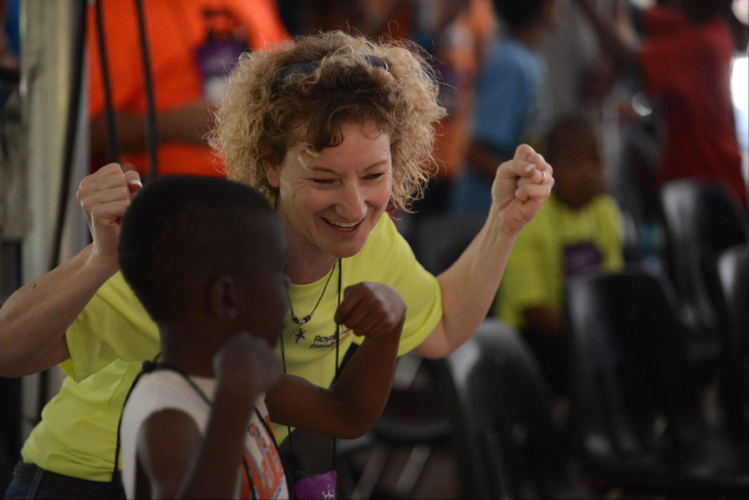 Royal Family Kids Camp director Carol Weber of St. Charles sings with one of the campers during breakfast club at the camp.
