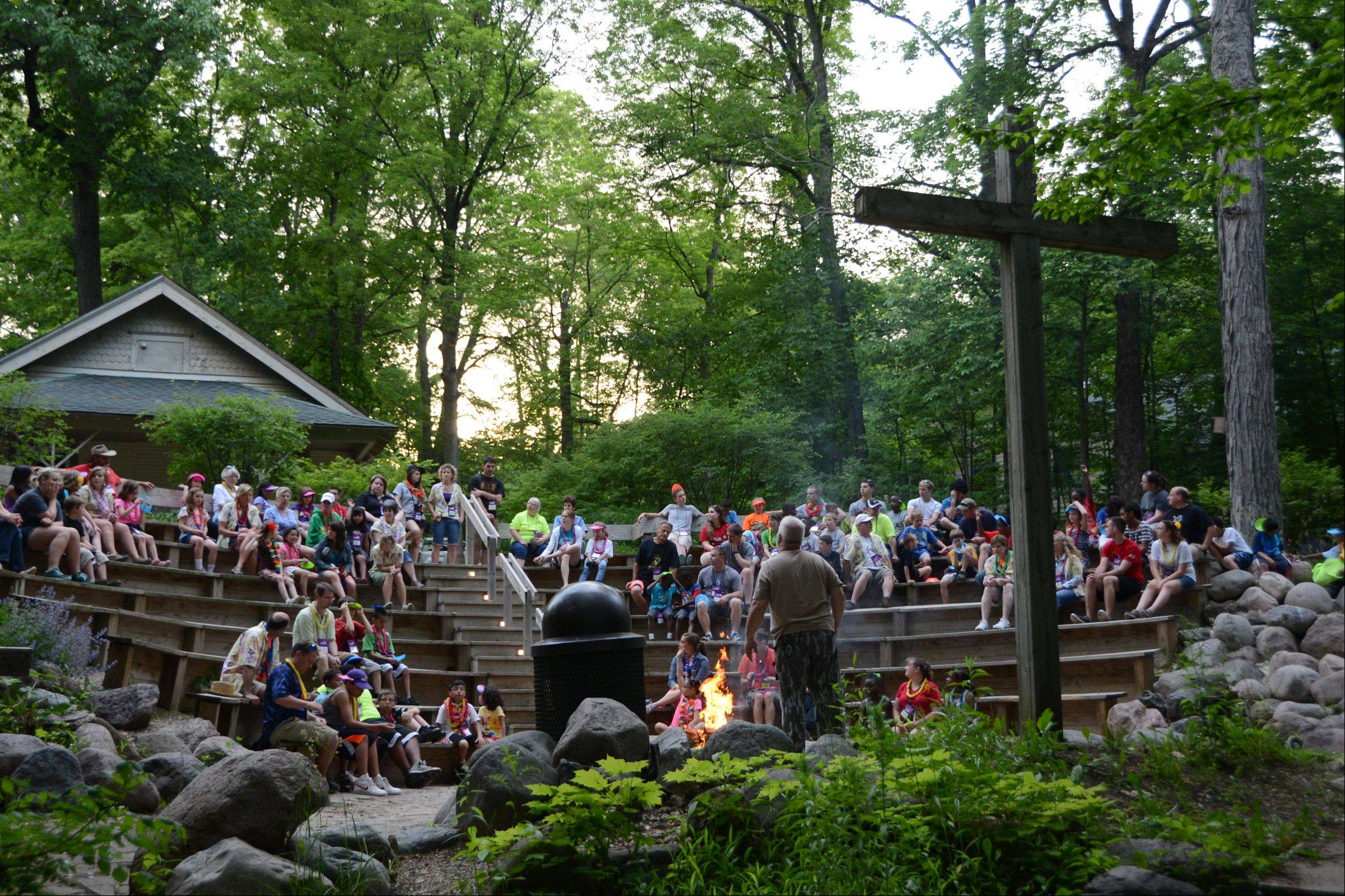 Royal Family Kids Camp volunteer Danny Sarros of Geneva leads campers and counselors in camp songs during the campfire time that ends the day. Campers and counselors talk about where they saw God in action at camp during the day.