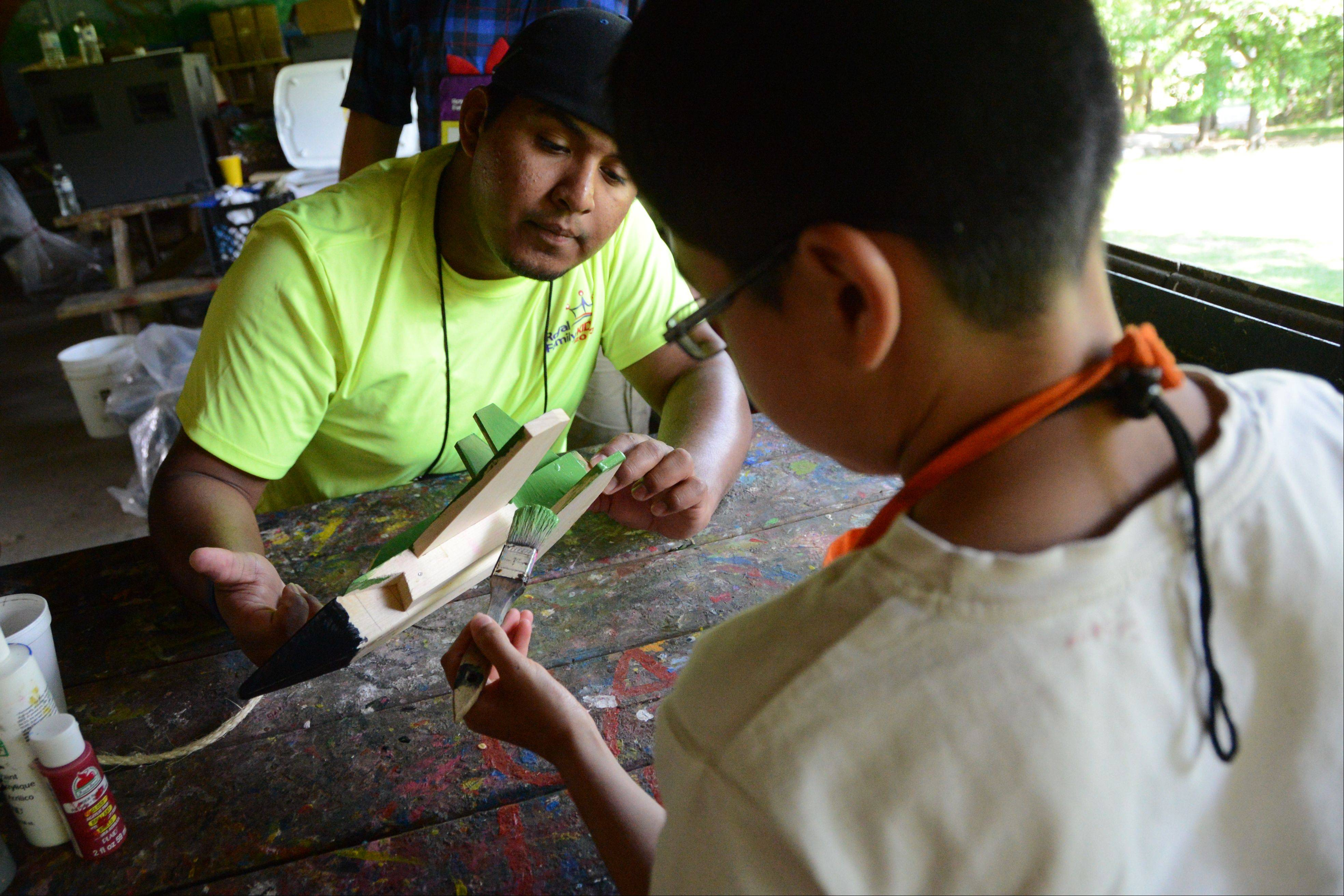 Royal Family Kids Camp counselor Andy Morado helps his camper build an airplane in the wood shop at the camp in Wisconsin.