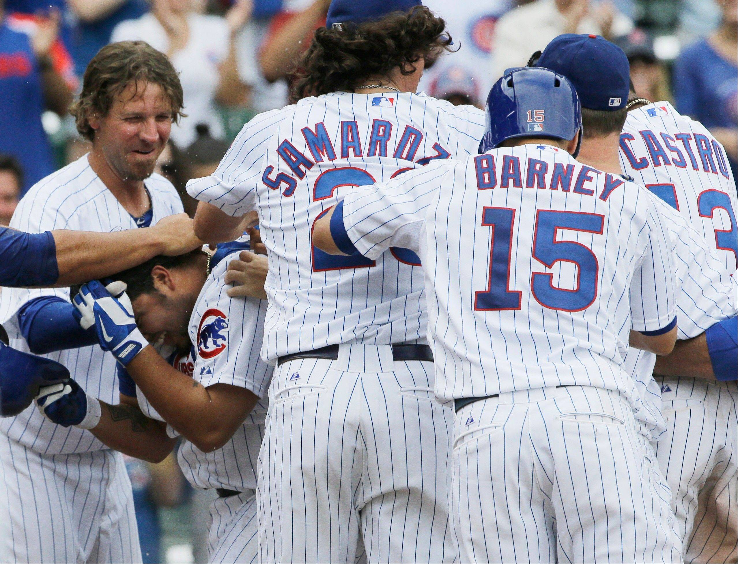 The Cubs' Dioner Navarro, lower left, celebrates with teammates after his game-ending sacrifice fly in the 11th inning Sunday at Wrigley Field.