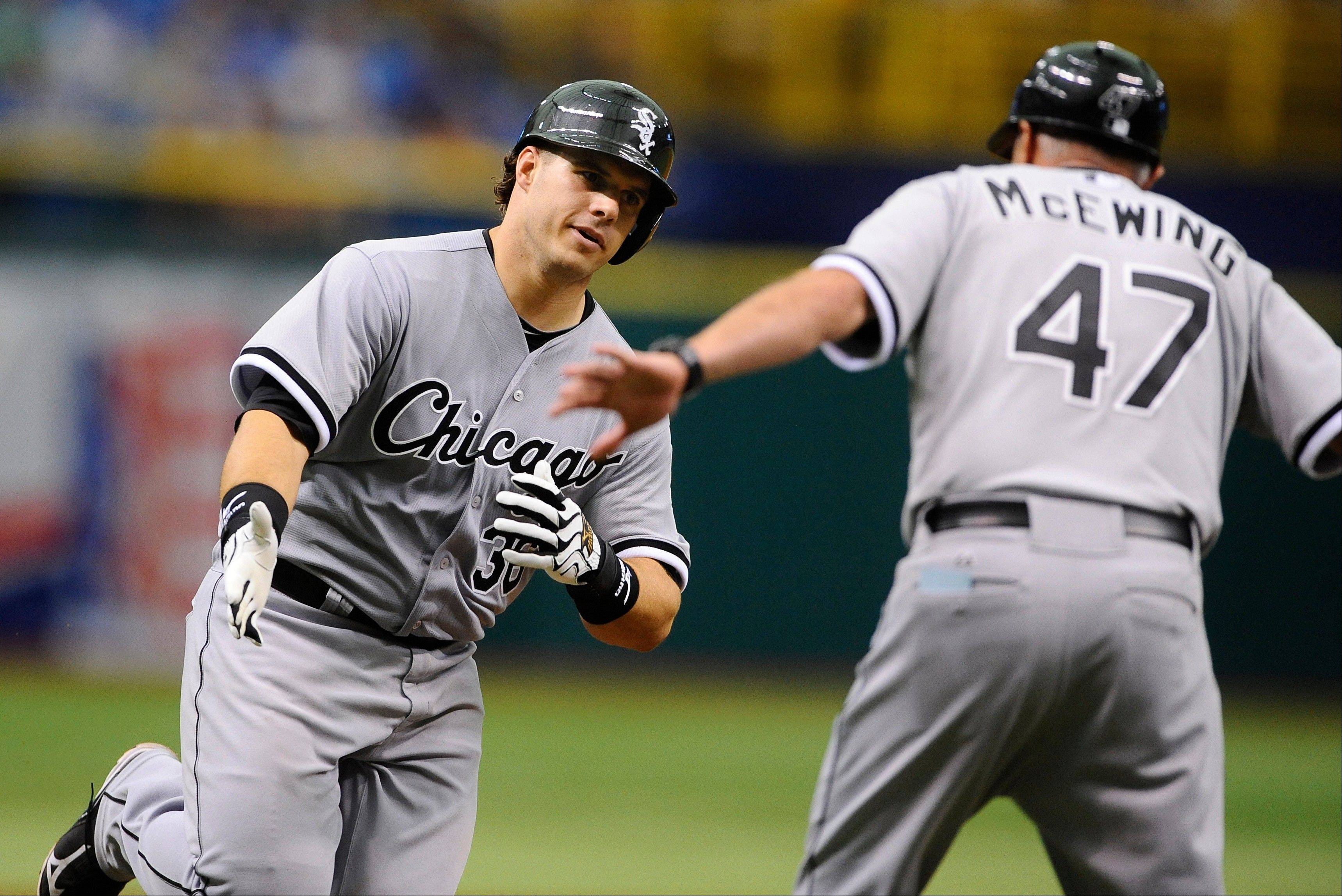 White Sox newbie Josh Phegley, left, celebrates with third base coach Joe McEwing while rounding the bases after hitting a home run off Tampa Bay Rays starting pitcher David Price during Sunday's sixth inning.