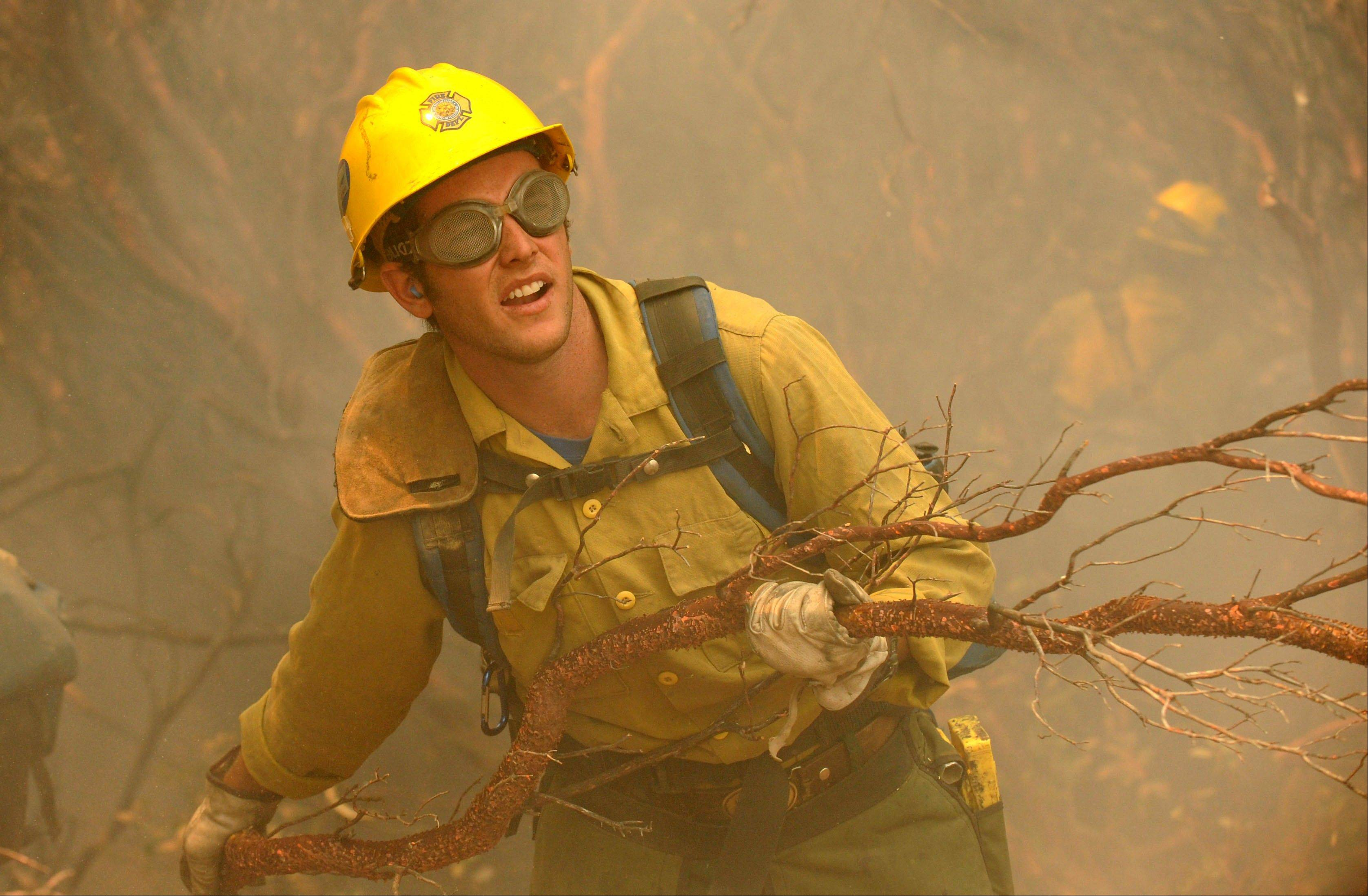 Rio Bravo Hotshot firefighter Cole Cates clears manzanita while cutting a fireline on the Telegraph Fire near Yosemite National Park in California in 2008.