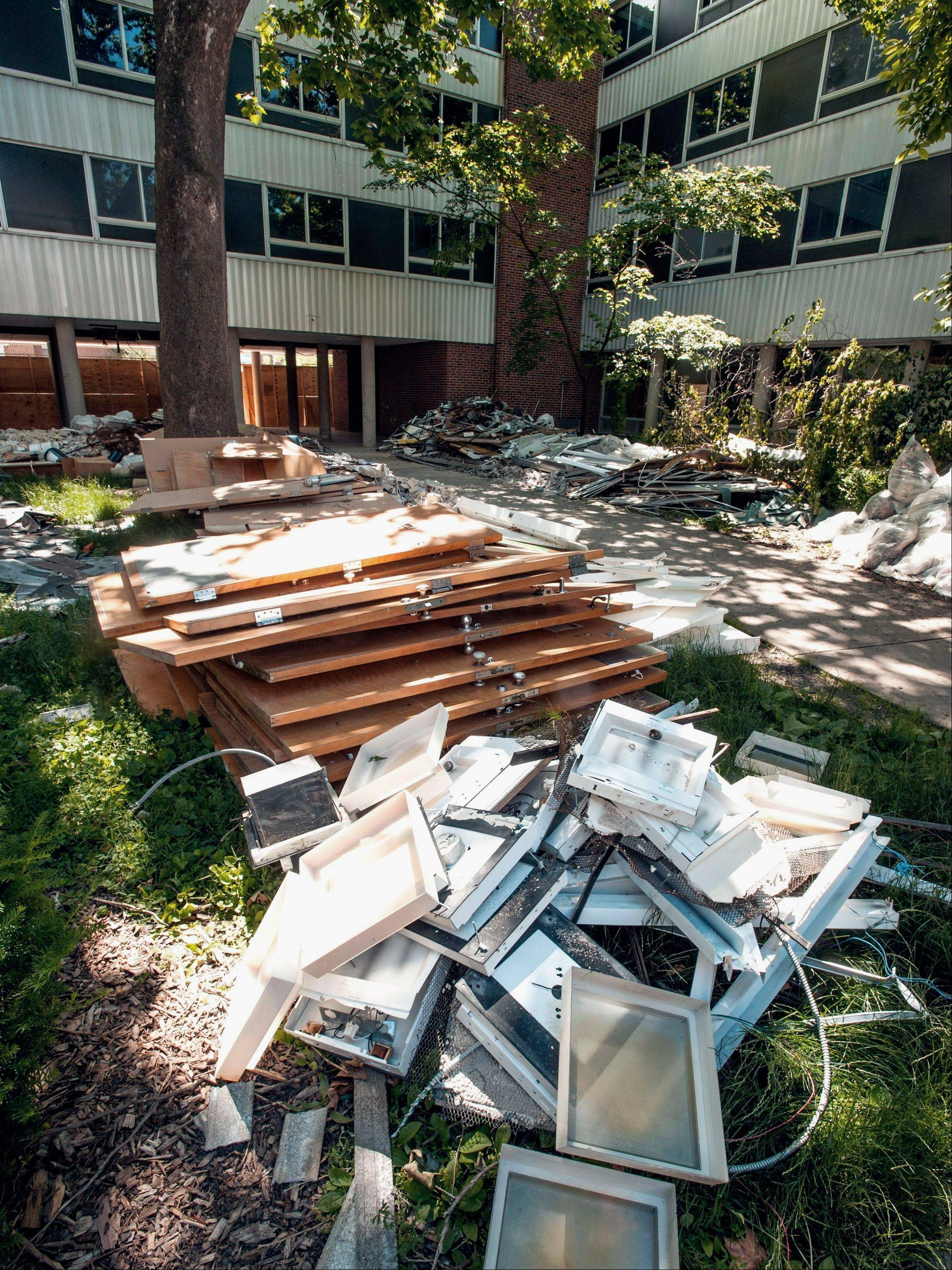 Material is separated into piles of metal and wood last month during the ongoing demolition of Forbes Hall on the University of Illinois campus in Champaign, Ill.