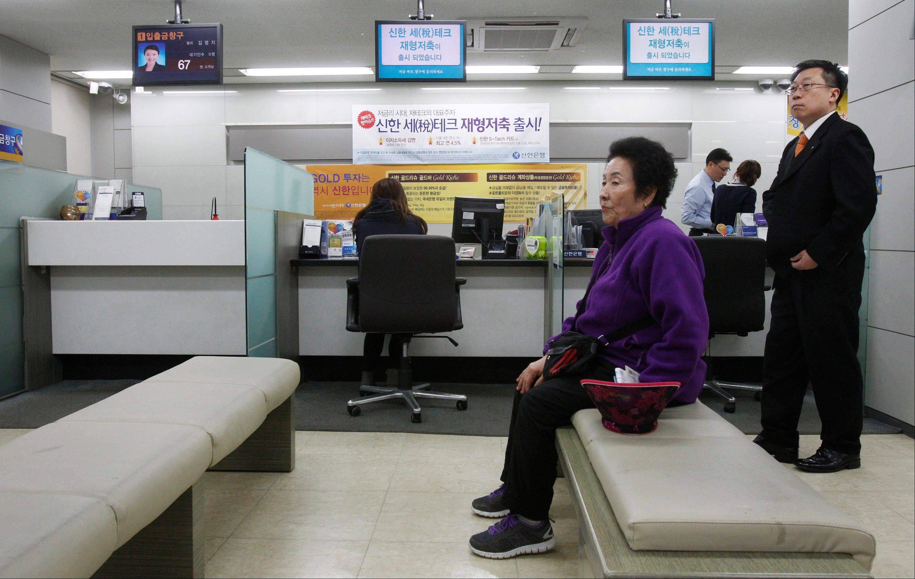 A customer sits in a branch of Shinhan Bank in Seoul, South Korea, after the bank's computer networks was paralyzed.