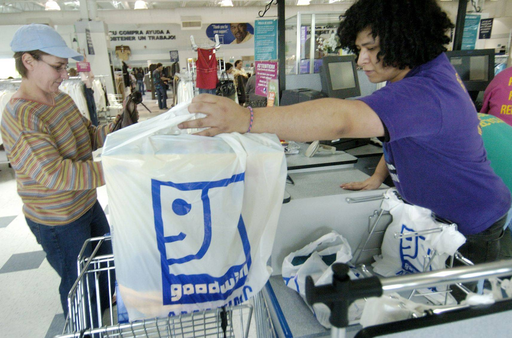 Tracee Breen, of Tower Lakes, pays cashier Pedro Rivera at the Goodwill store in Mundelein. A Goodwill retail store and donation center is to open in the Hoffman Village Shopping Center, near Barrington and Golf roads.