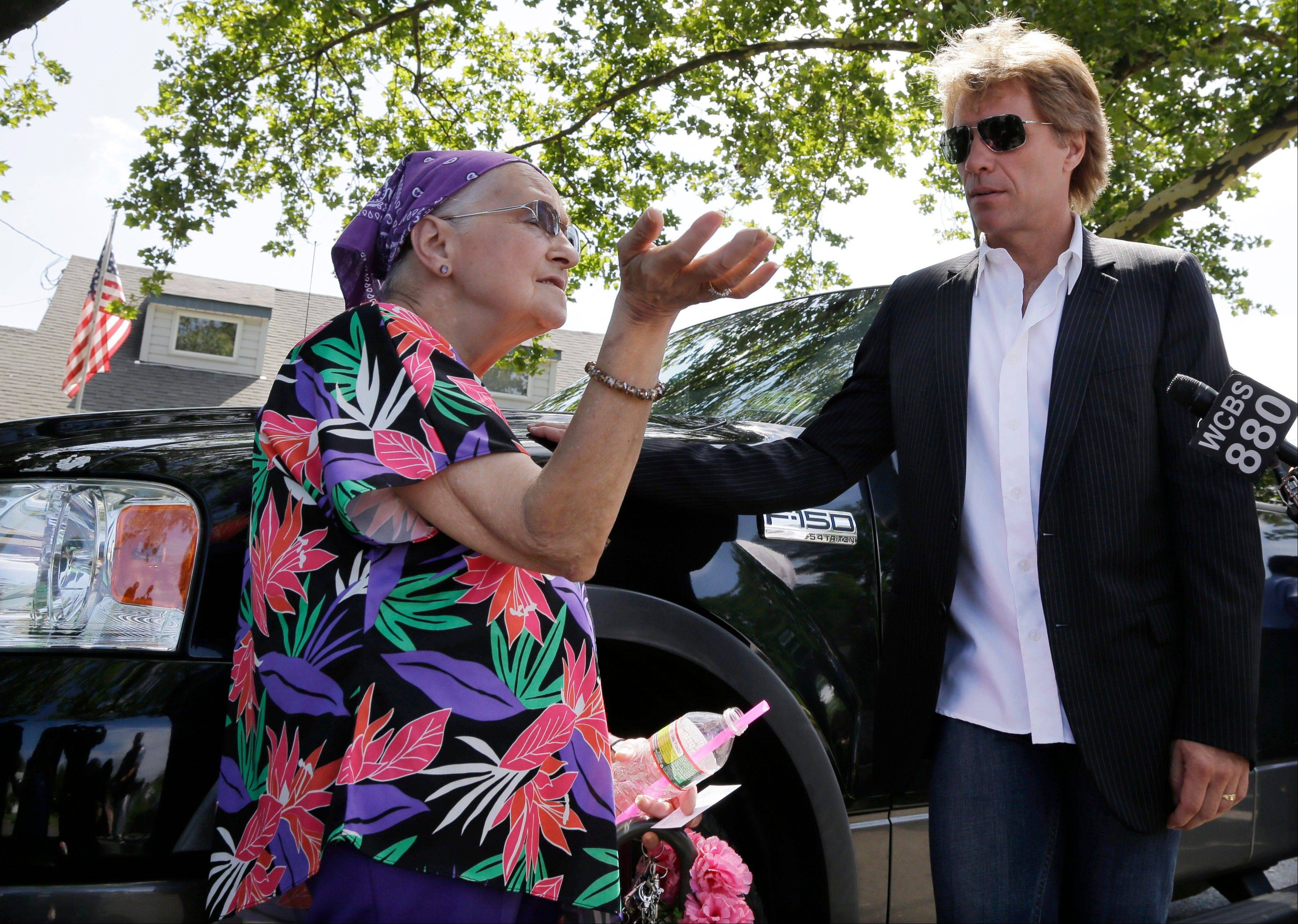 Sharon Mary Atkinson describes some of the devastation from Superstorm Sandy to singer Jon Bon Jovi, right, as he walked through his hometown of Sayreville, N.J., with New Jersey Gov. Chris Christie. Bon Jovi is giving $1 million to help the band's home state recover from Superstorm Sandy.