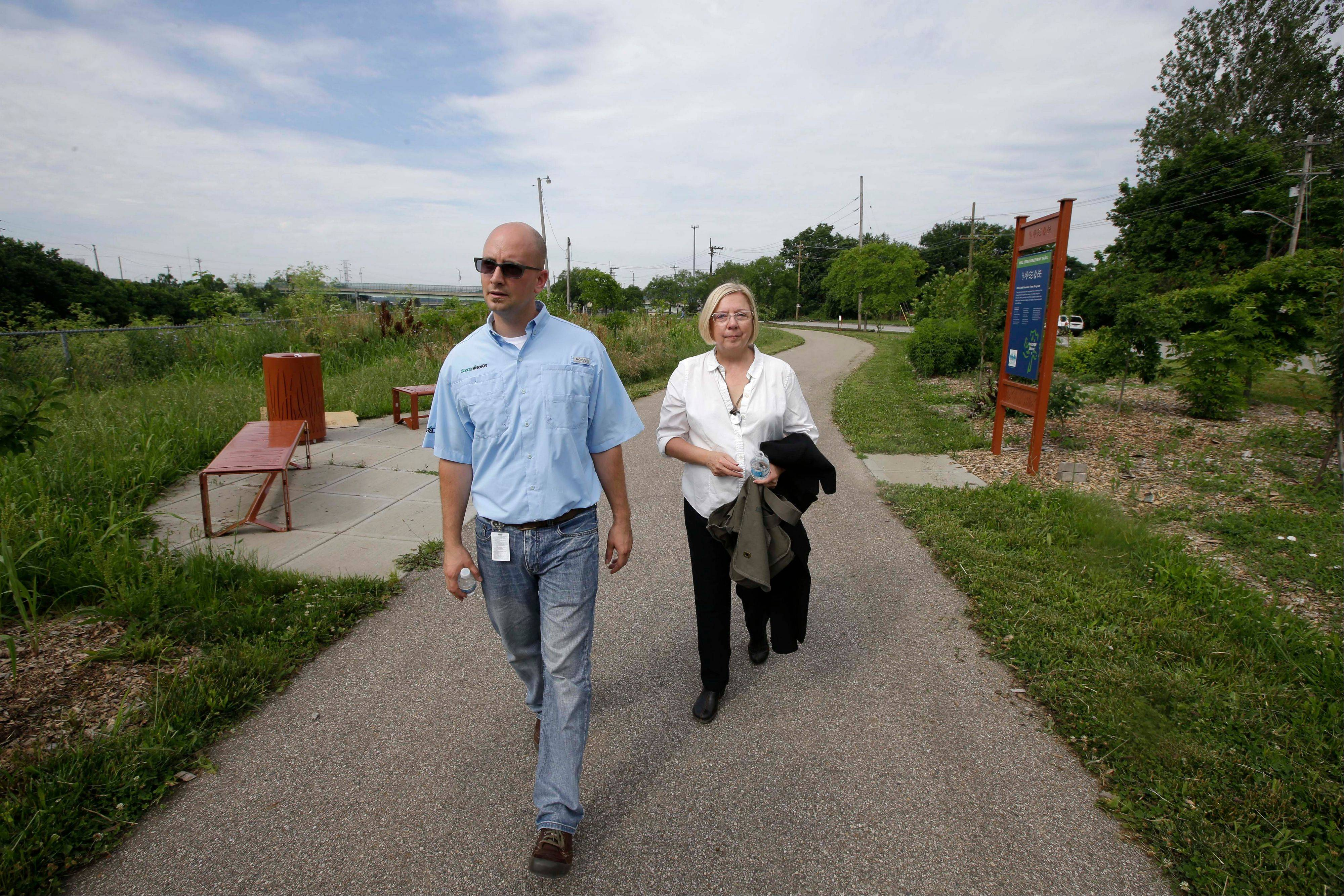 Scotts Miracle-Gro representative Chris Cerveny, left, and Robin Corathers of Groundwork Cincinnati walk along the Mill Creek Greenway, in Cincinnati. The city of Cincinnati, with the help of ScottsMiracle-Gro's GRO1000 program, is revitalizing the area near the creek that runs through industrial areas and has long been a problem due to deforestation, pollution and sewer overflow.