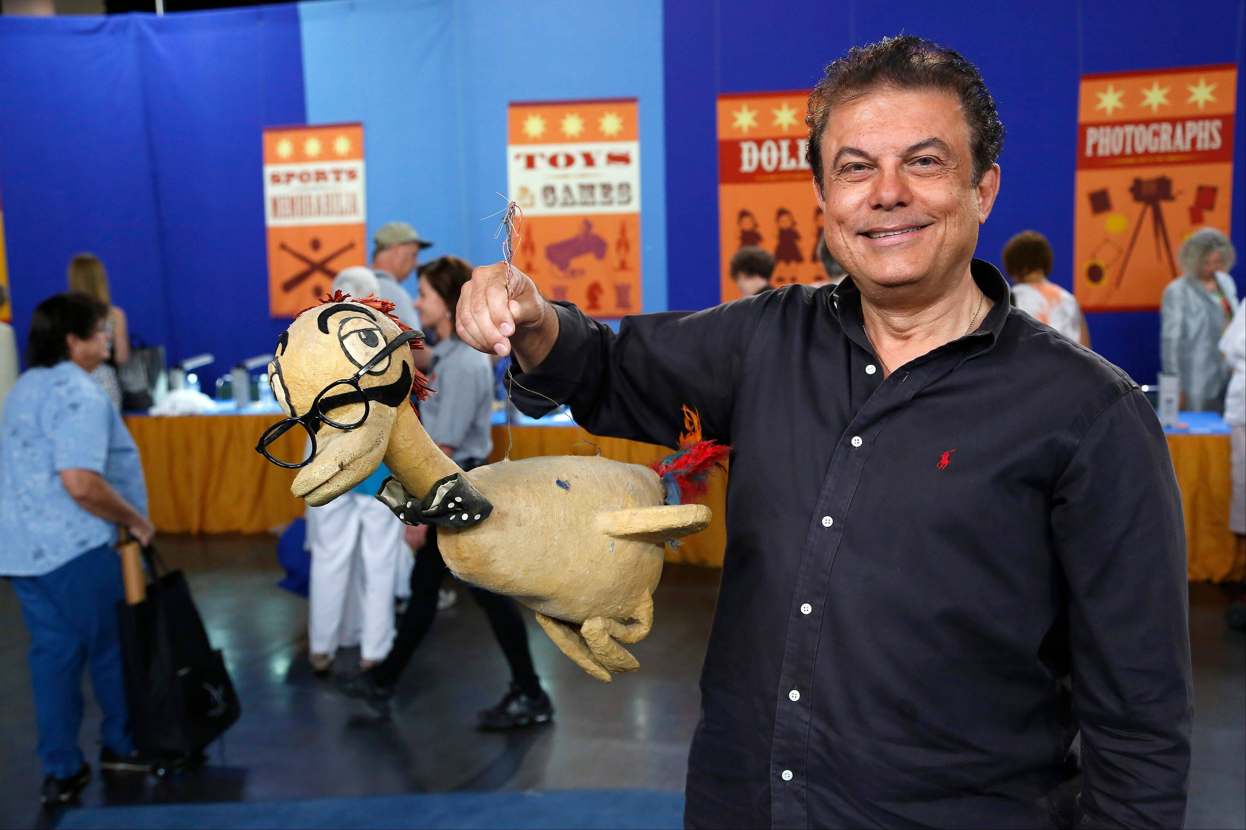 "Joe holds a Marx Brother prop duck during the taping of the popular appraisal show ""Antiques Roadshow,"" in Anaheim, Calif. The top-rated PBS series is on the move, taping programs in eight U.S. cities for its upcoming 18th season."
