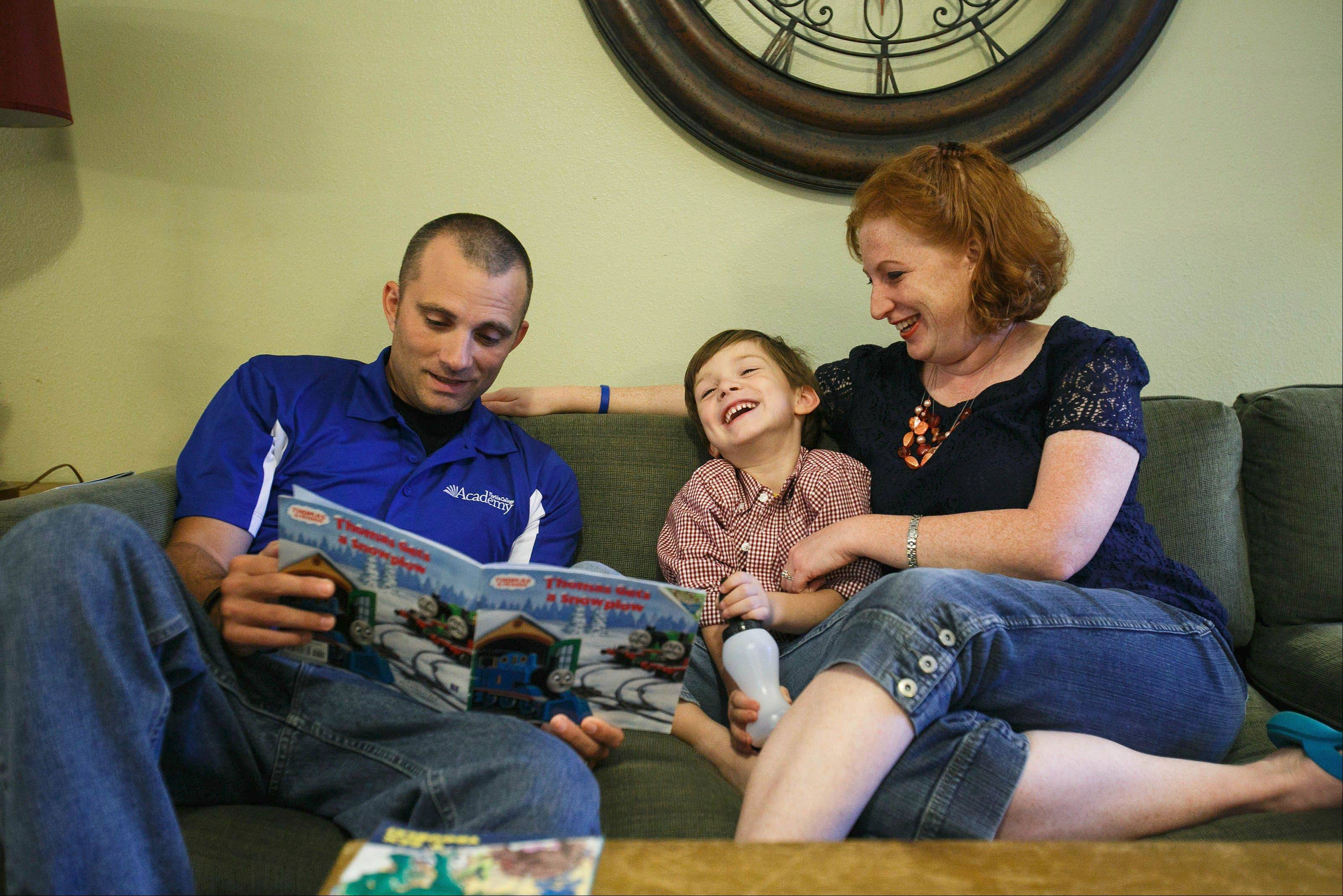 Josh Hastings, left, who was diagnosed with Stage 3 colon cancer, reads to his son Conner while relaxing on the couch with his wife, Andrea, at their home.