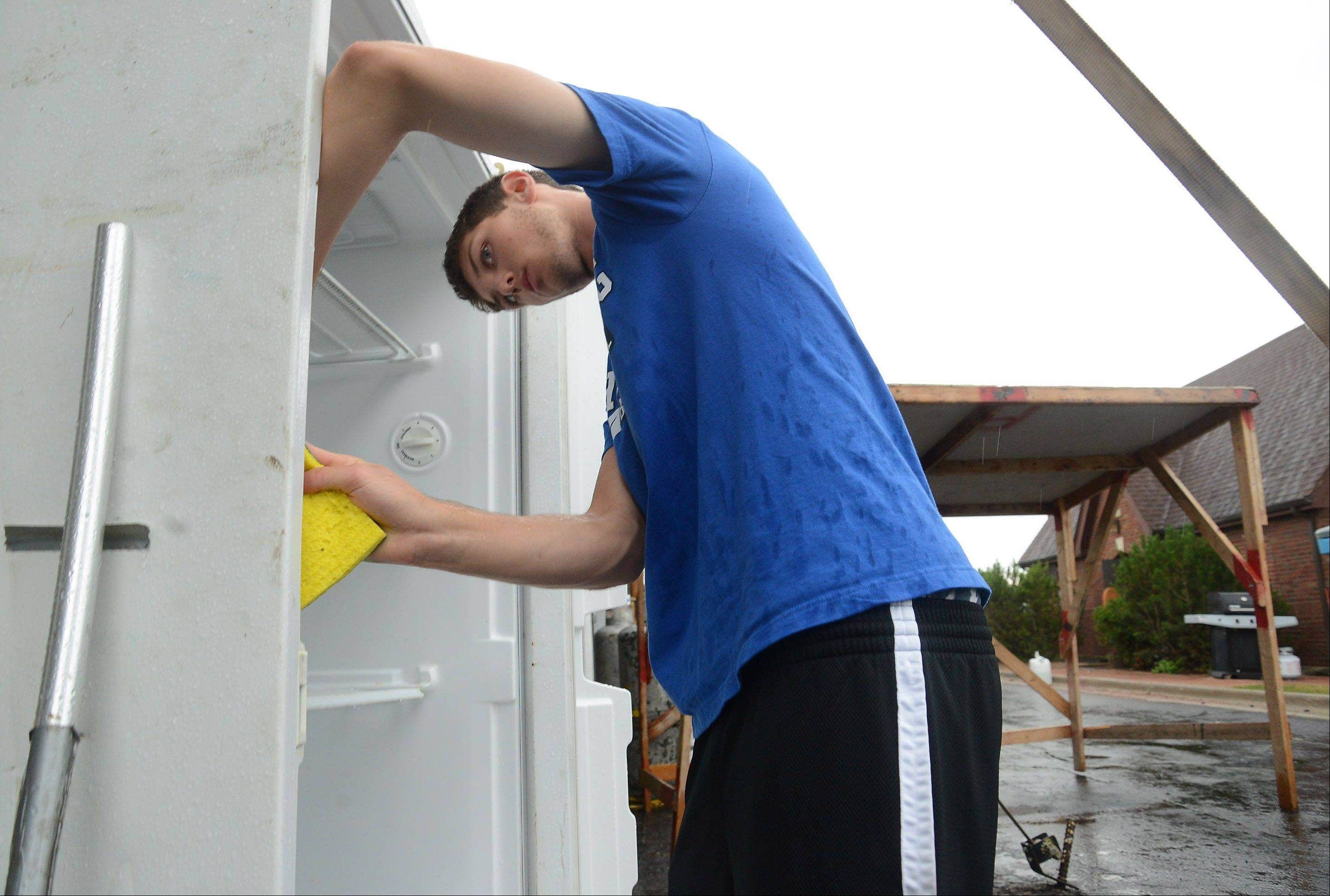 Justin Webb, of Wheeling High School boys basketball, washes down a cooler.