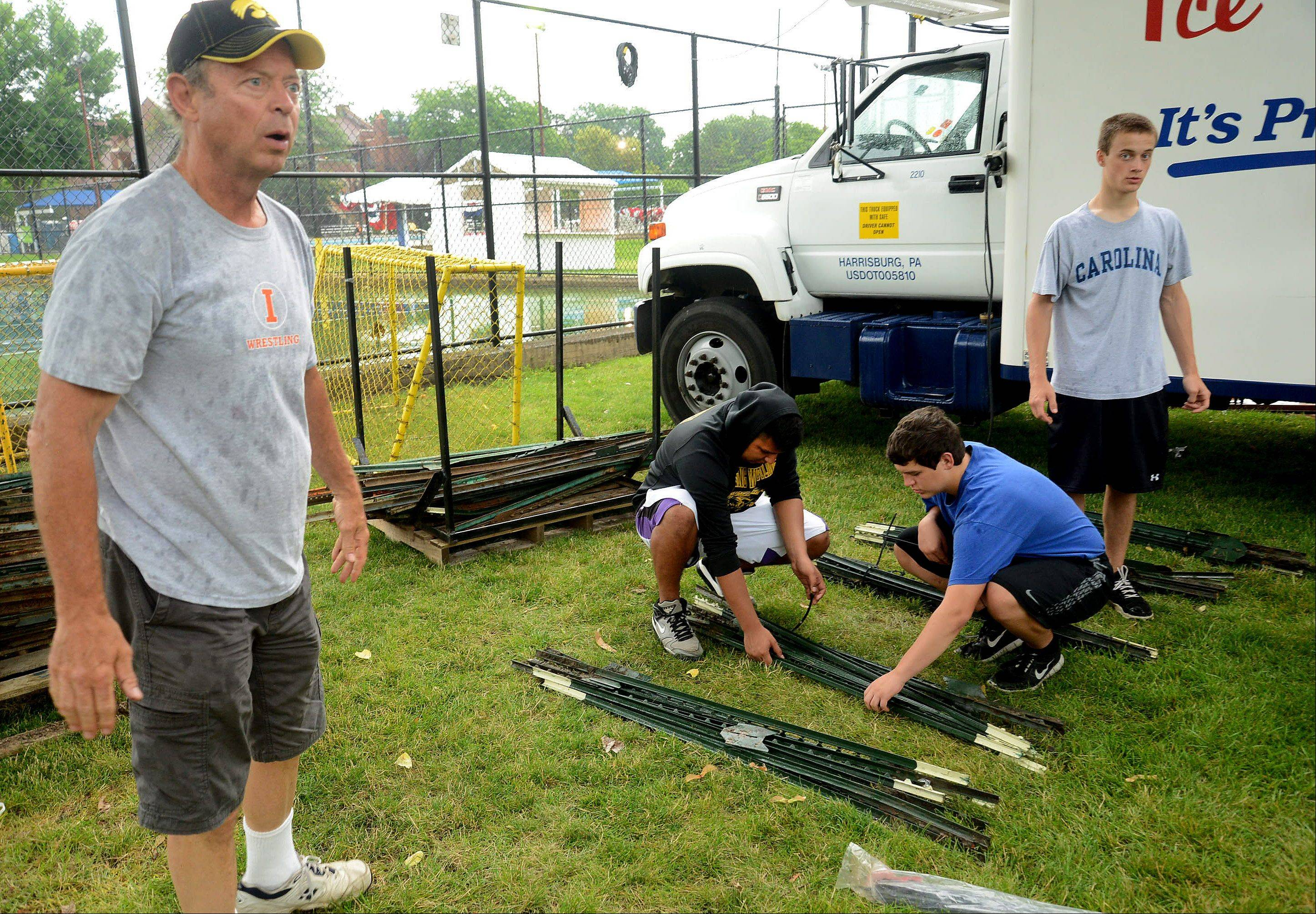 Dave Froehlich, head wrestling coach at Rolling Meadows High School, helps his wrestlers from left, Ruben Guerrero, Grant Palmer and Dan Stubing clean up after Frontier Days.