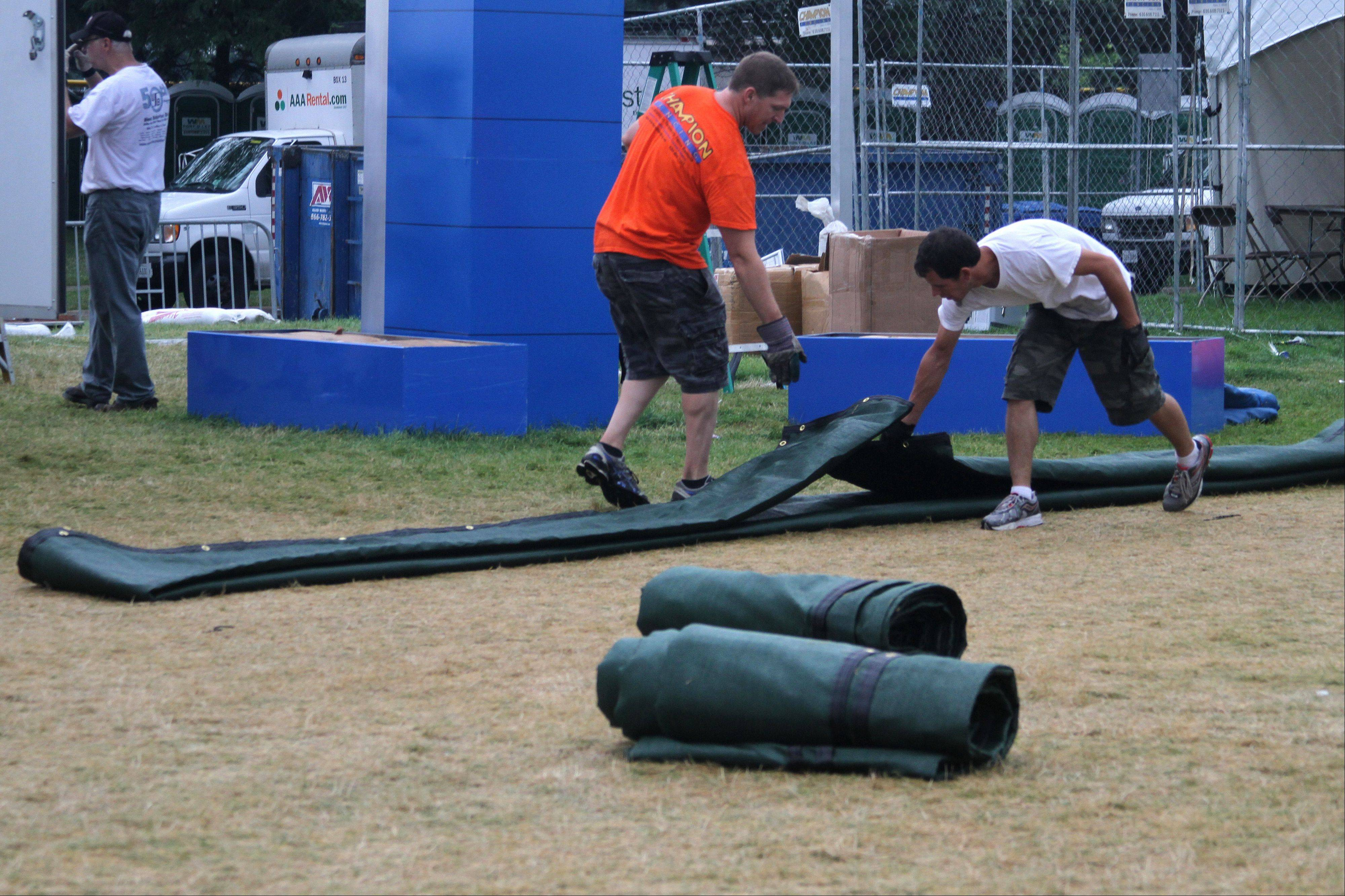 Crews roll up a tarp Monday as a part of Ribfest cleanup at Knoch Park in Naperville.