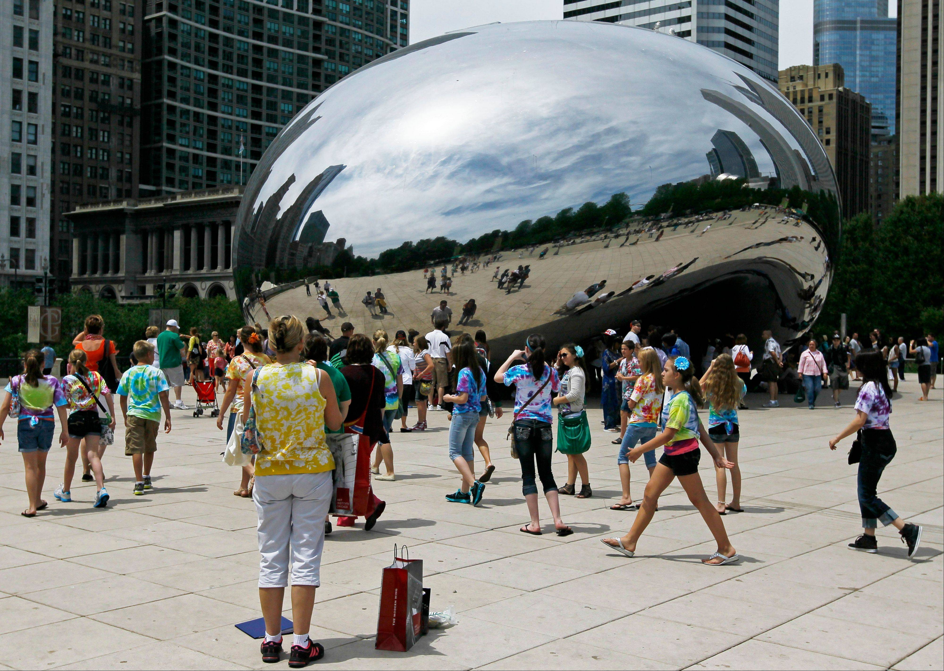 "Visitors at Millennium Park enjoy the sculpture ""Cloud Gate,"" also known as ""The Bean,"" last summer in Chicago. Millennium Park is one of several free attractions in the city."