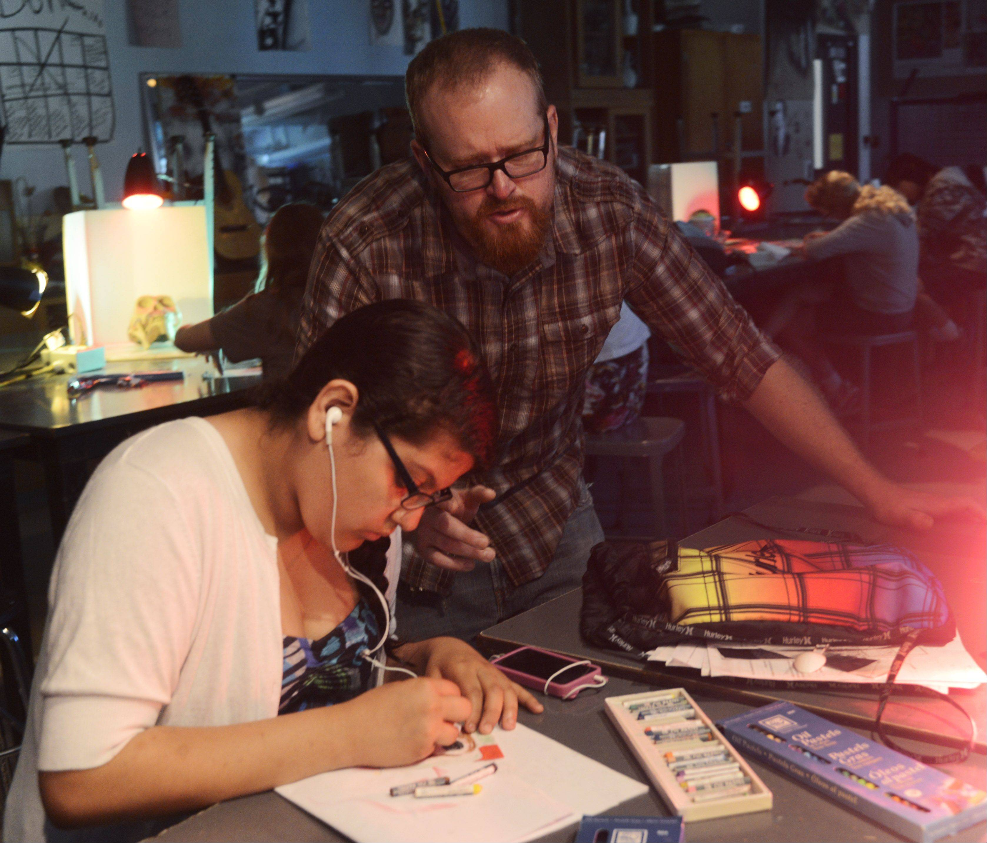 July Top Teacher Jason Burke of Barrington High School gives advice to freshman Jenny Torrez as she sketches a still life.