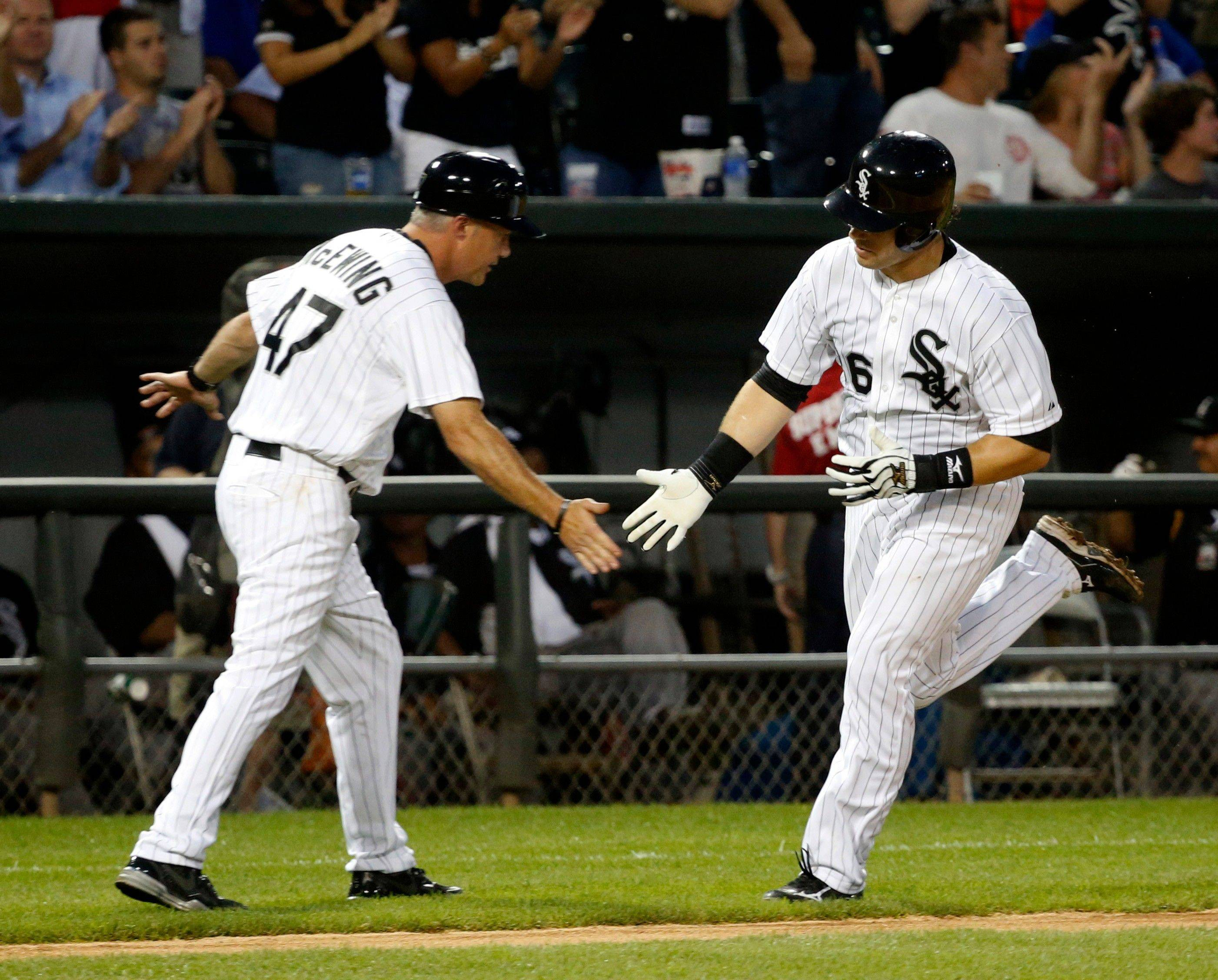 White Sox catcher Josh Phegley is greeted by third-base coach Joe McEwing after Phegley's home run off Cubs starting pitcher Matt Garza during the third inning of an interleague baseball game Monday night at U.S. Cellular Field.