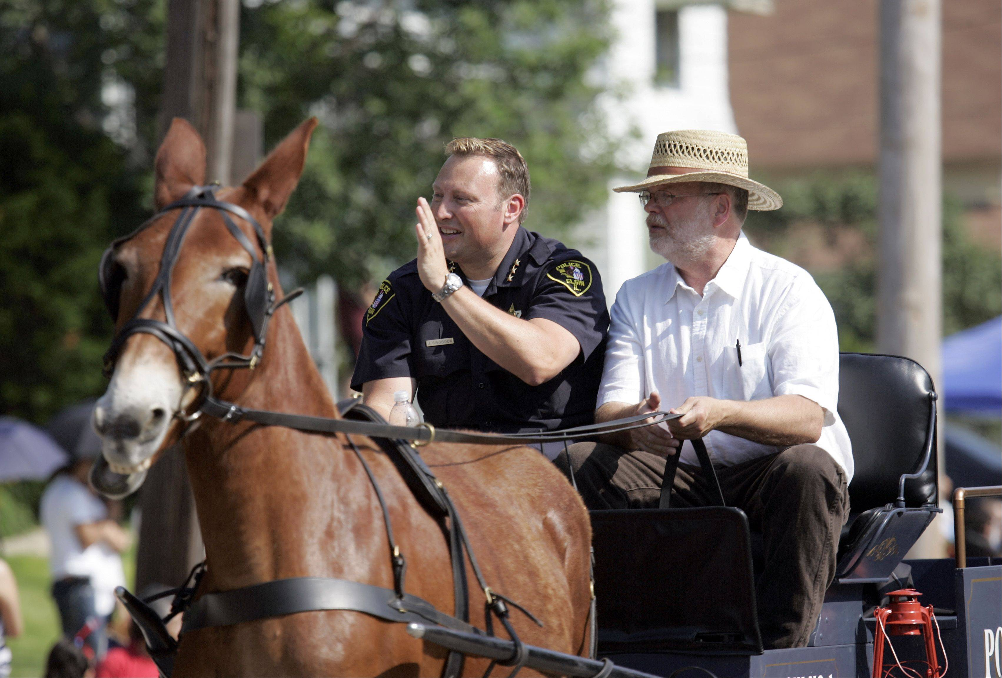 Elgin Police Chief Jeff Swoboda, left, waves to the crowd during the Elgin Fourth of July Parade.