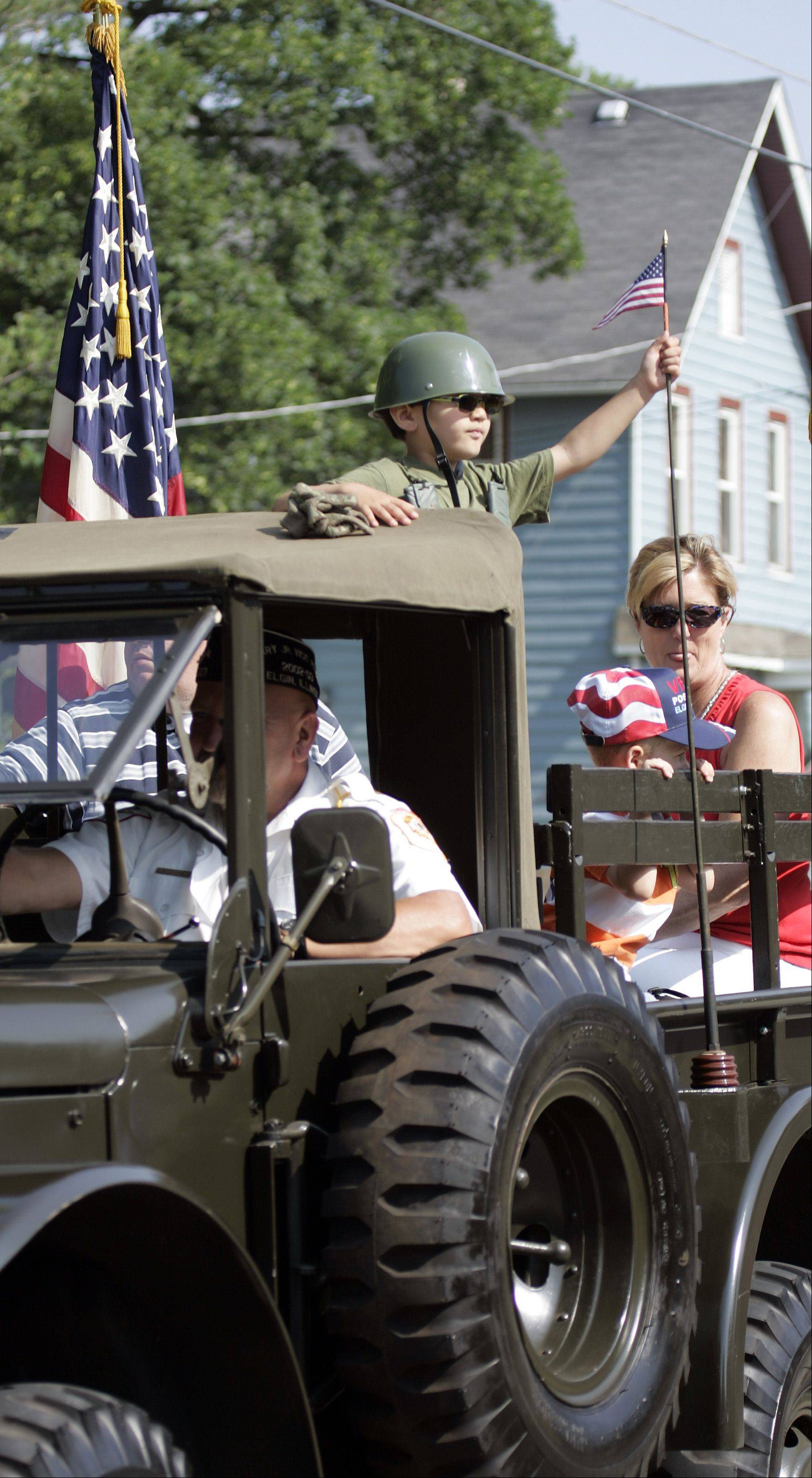 Perched atop a military vehicle, 3-year-old Parker Balk waves his flag during the Elgin Fourth of July Parade.