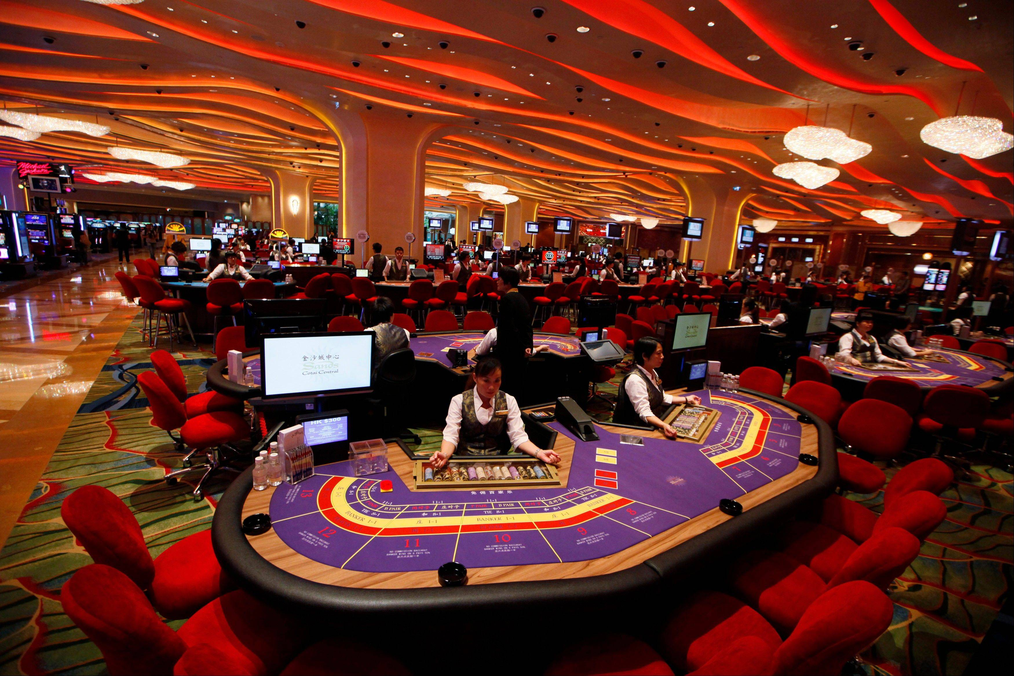 Croupiers sit at a baccarat gaming table inside a casino during the opening day of Sheraton Macao Hotel at the Sands Cotai Central in Macau. Macau is in the midst of one of the greatest gambling booms the world has ever known.