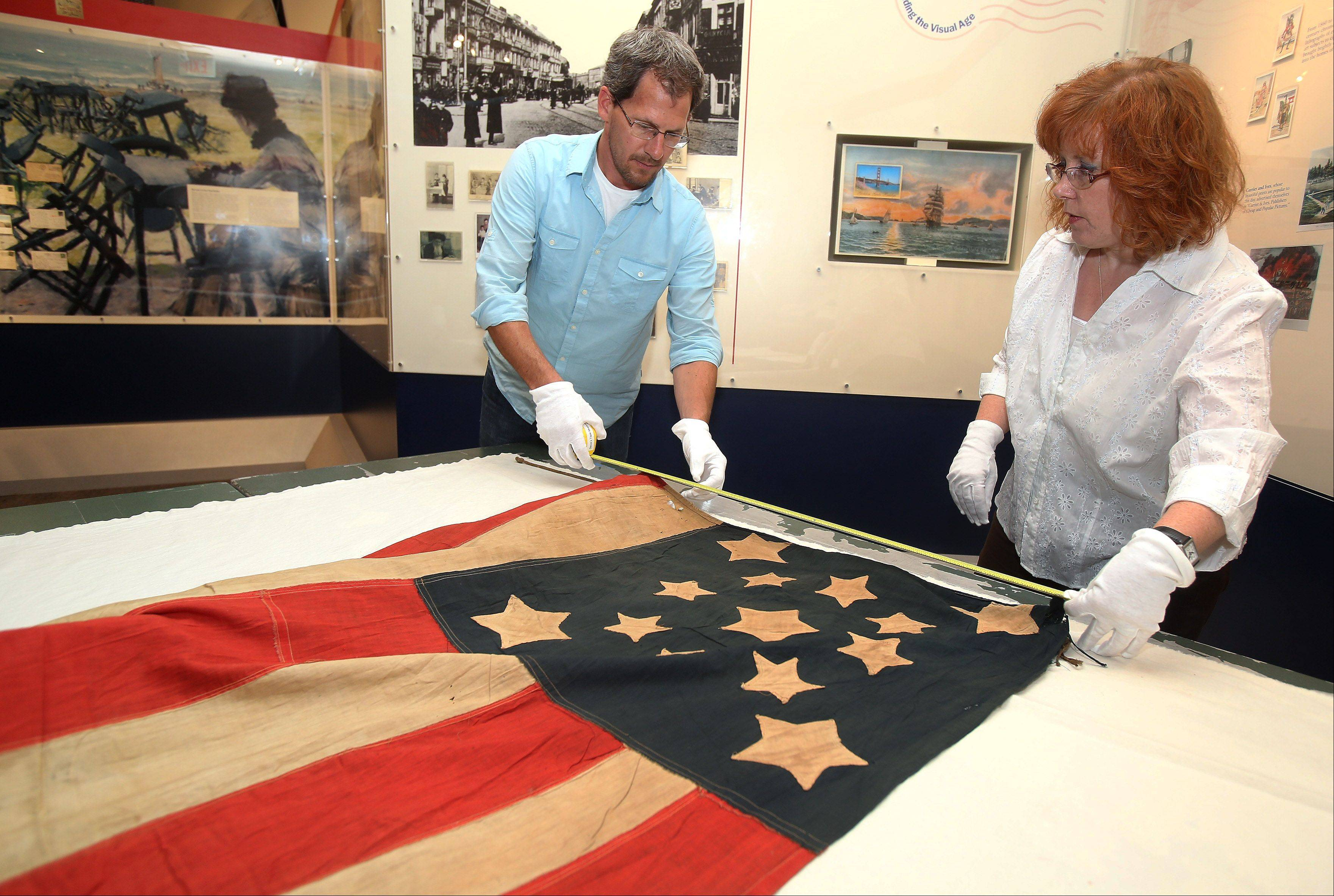 Exhibits manager Steve Furnett and collections coordinator Diana Detske prepare a Civil War flag for viewing Wednesday at the Lake County Discovery Museum near Wauconda. The flag was donated by descendants of Civil War veteran Edward Murray after it was found hidden in a shoe box.