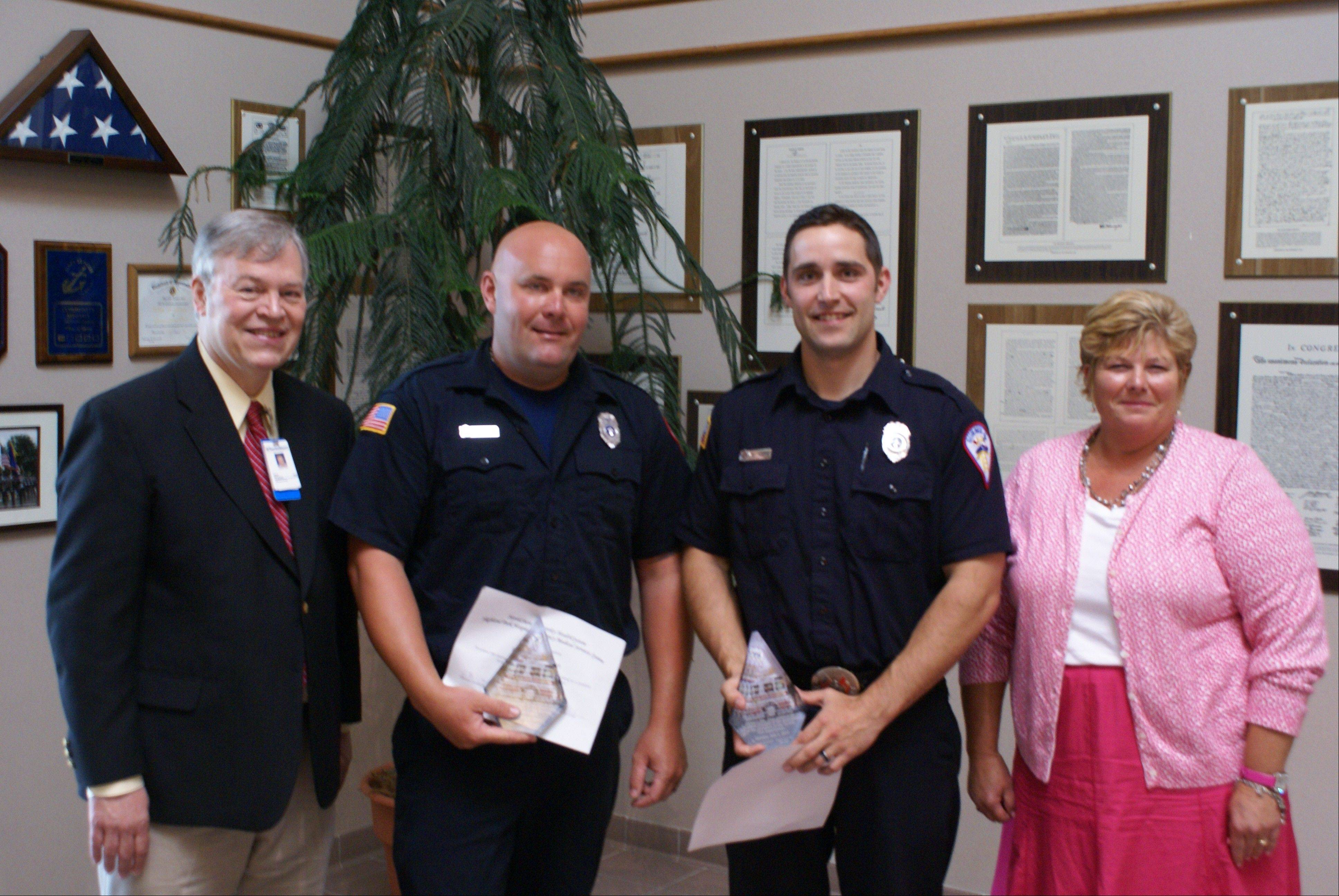 From left to right, Dr. Jack Whitney, NorthShore University HealthSystem emergency medical services director, Gurnee firefighter/paramedics Robert Davidson and Scott Rans, and NorthShore registered nurse and EMS coordinator Cheri Smirles at Monday's Gurnee village board meeting, when Davidson and Rans were honored for performing lifesaving actions while off duty in May.