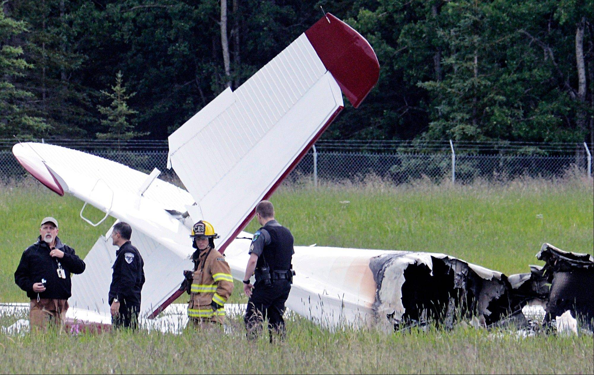 Police and emergency personnel stand near the remains of a fixed-wing aircraft that was engulfed in flames Sunday July 7, 2013 at the Soldotna Airport in Soldotna, Alaska. The crash killed all 10 passengers.