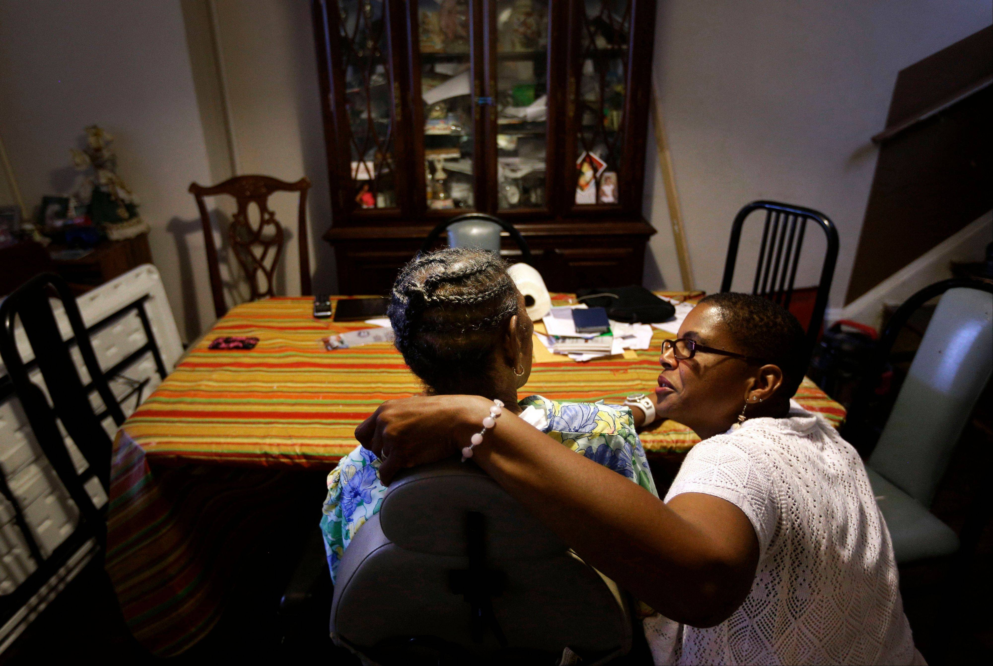 Occupational therapist Ally Evelyn-Gustave, right, speaks with Alberta Hough, who suffers from Parkinson's disease, in Hough's home in Baltimore. Hough struggles to feed herself a snack, her arms shaking badly from Parkinson's disease.