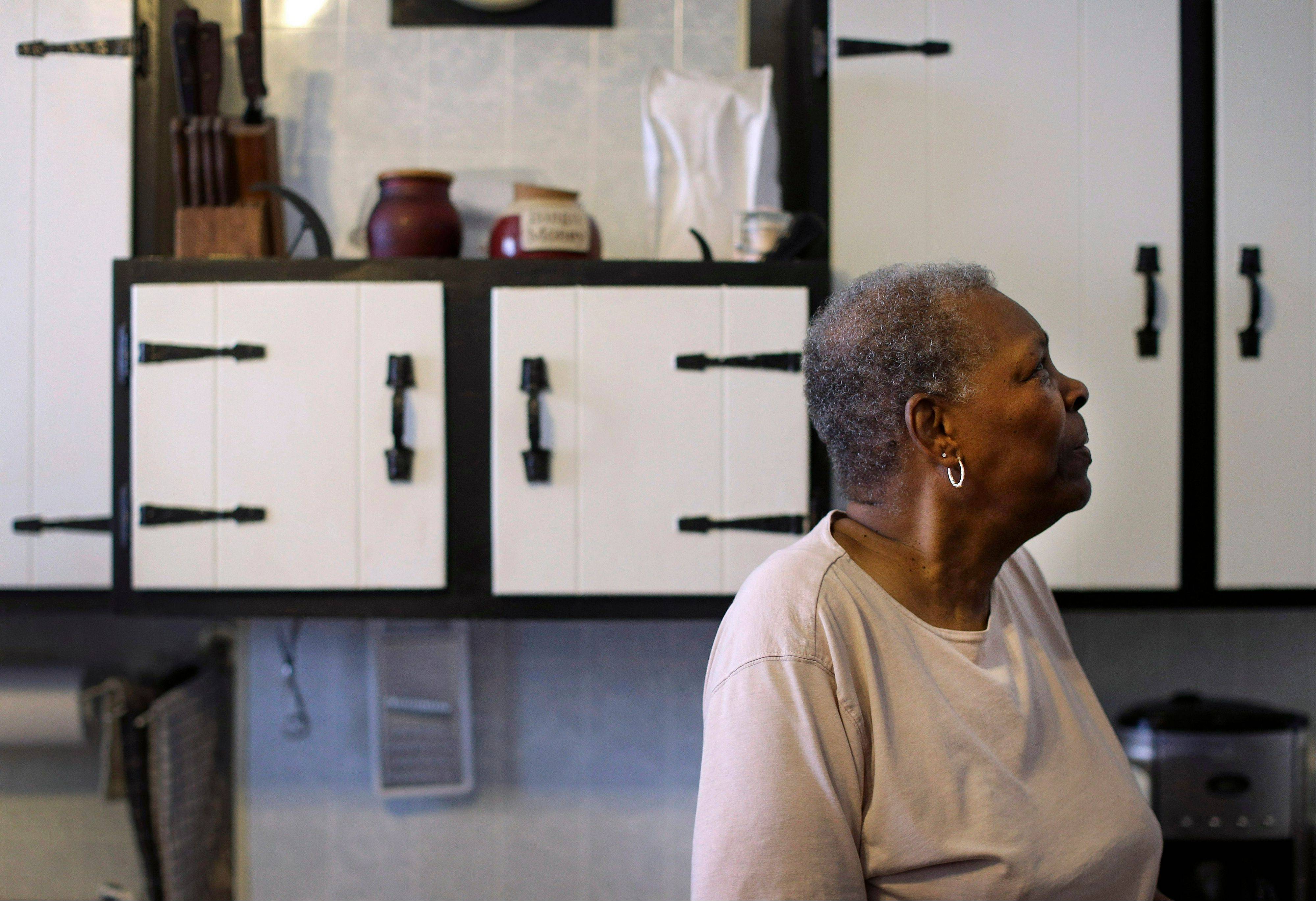 Hattie Watties in front of cabinets that were lowered in her kitchen in Baltimore, allowing her easier access to items inside that she once struggled to reach on her own. Physical limitations become more difficult with doorways too narrow for walkers, toilets that are lower than chairs, and kitchen counters too tall to sit while cooking.