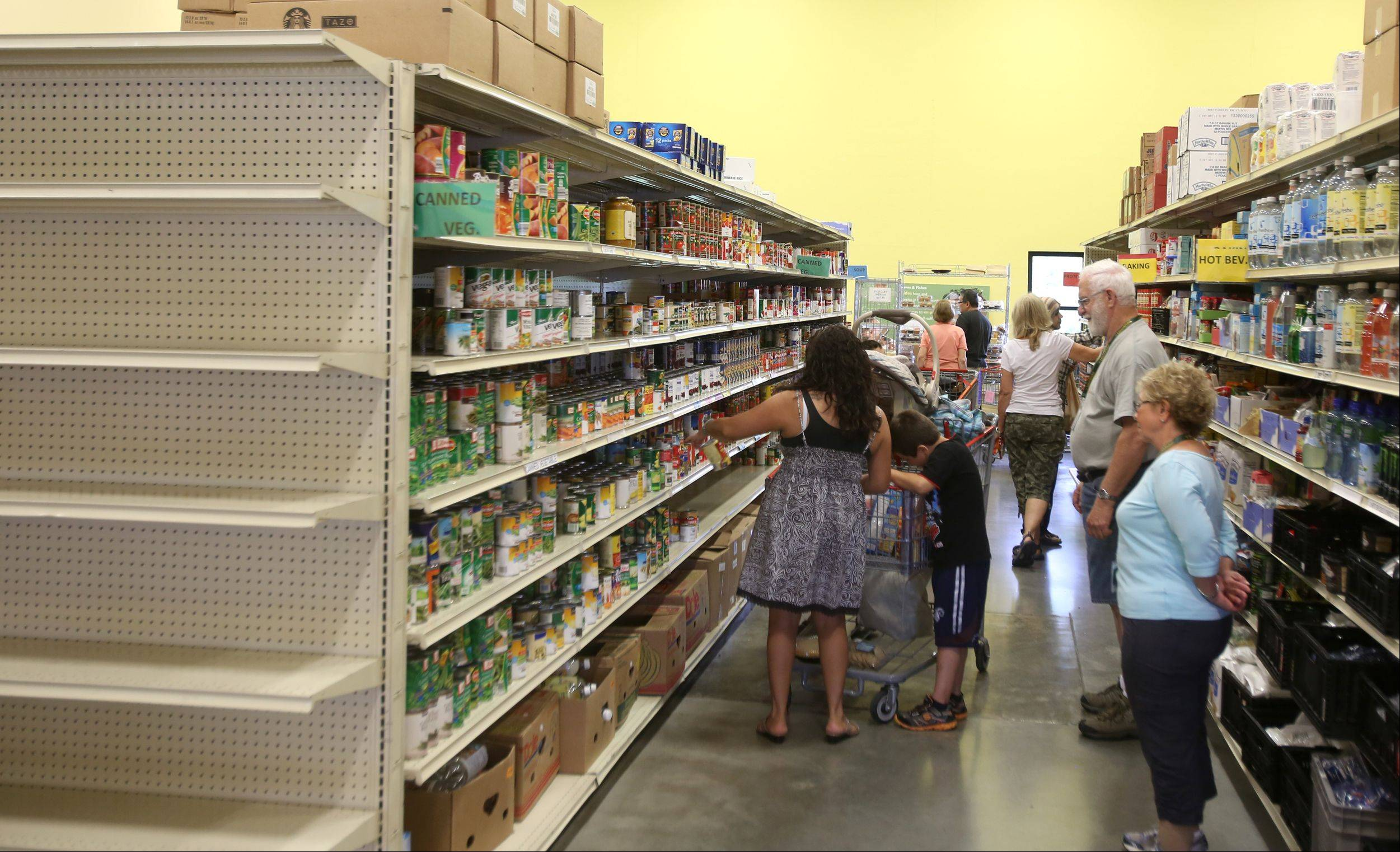Volunteers help pantry visitors shop for groceries Tuesday at Loaves & Fishes Community Pantry in Naperville.