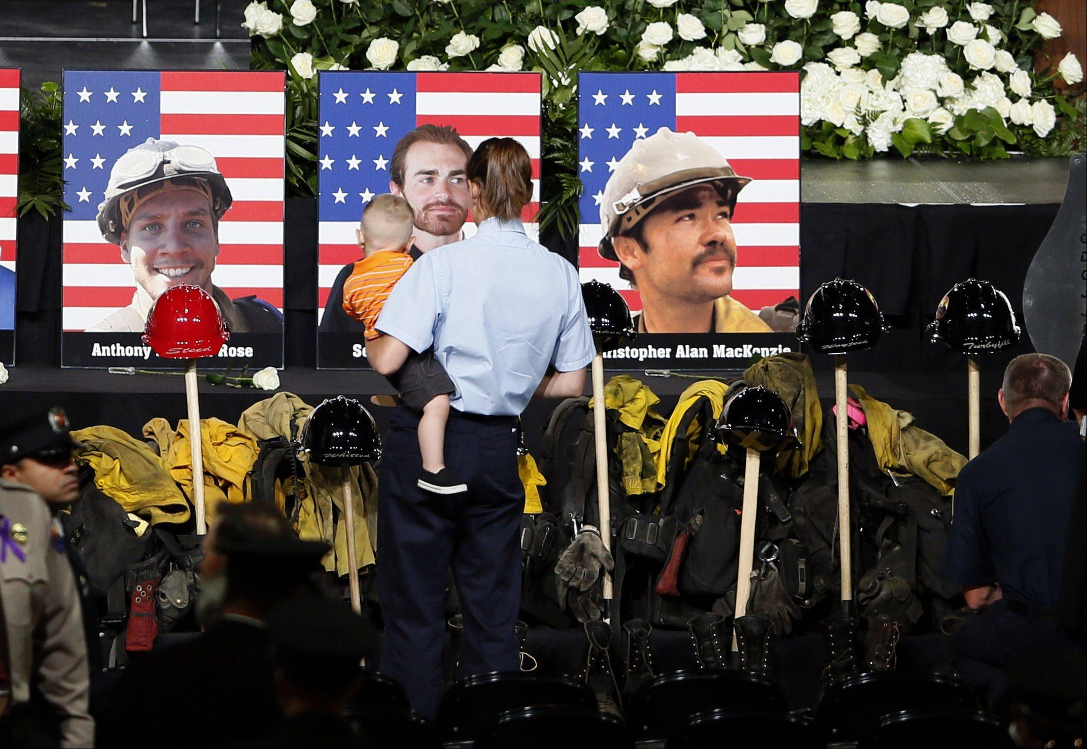 A woman pays her respects in front of photos of the fallen members of the Granite Mountain Hotshots, including former Beach Park resident Anthony Rose at left, at a memorial service in Prescott Valley, Arizona July 9, 2013.