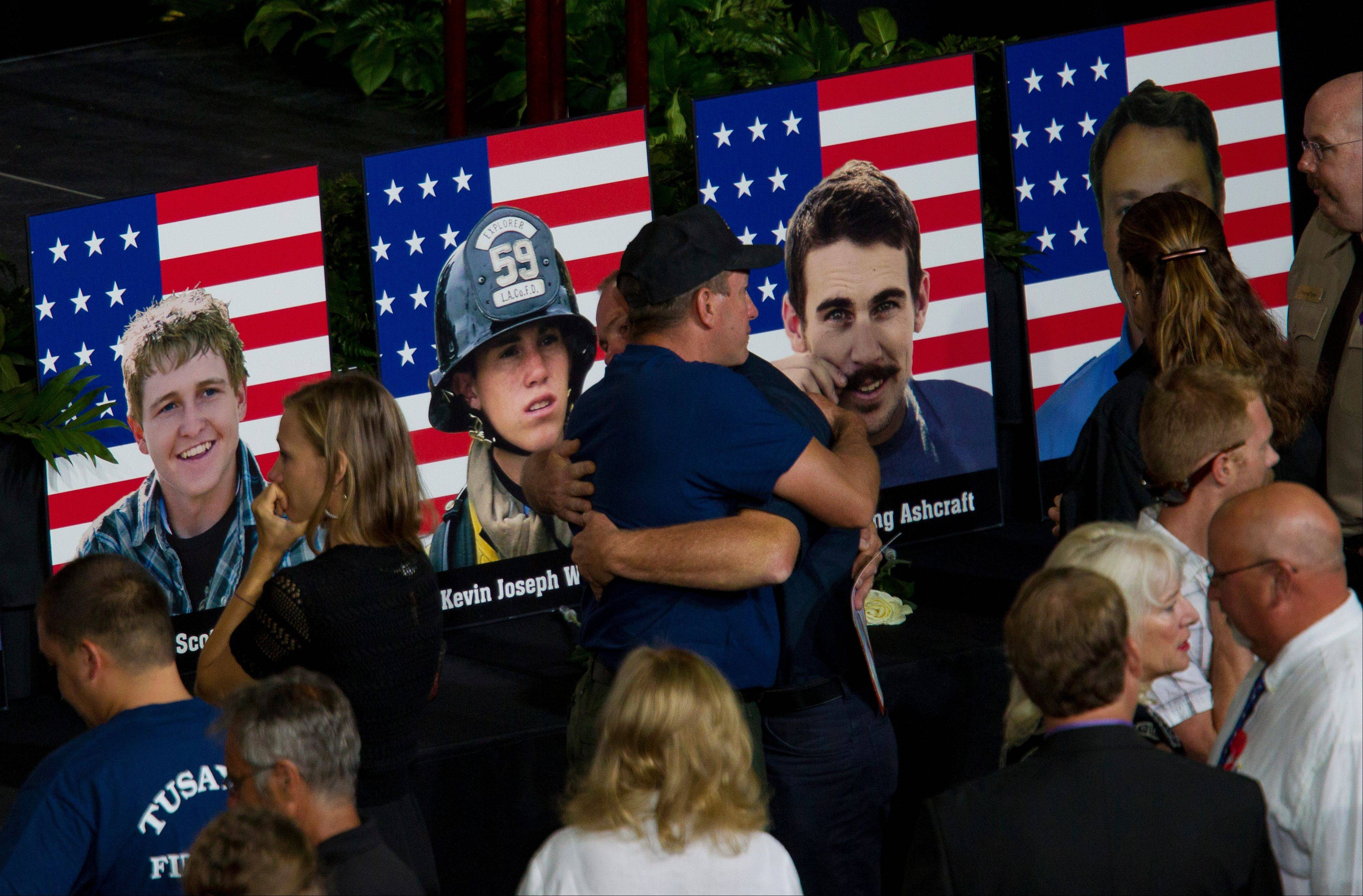 Photos of some of the 19 fallen firefighters line the front of the stage before a memorial service for the 19 fallen firefighters at Tim's Toyota Center in Prescott Valley, Ariz. on Tuesday, July 9, 2013.