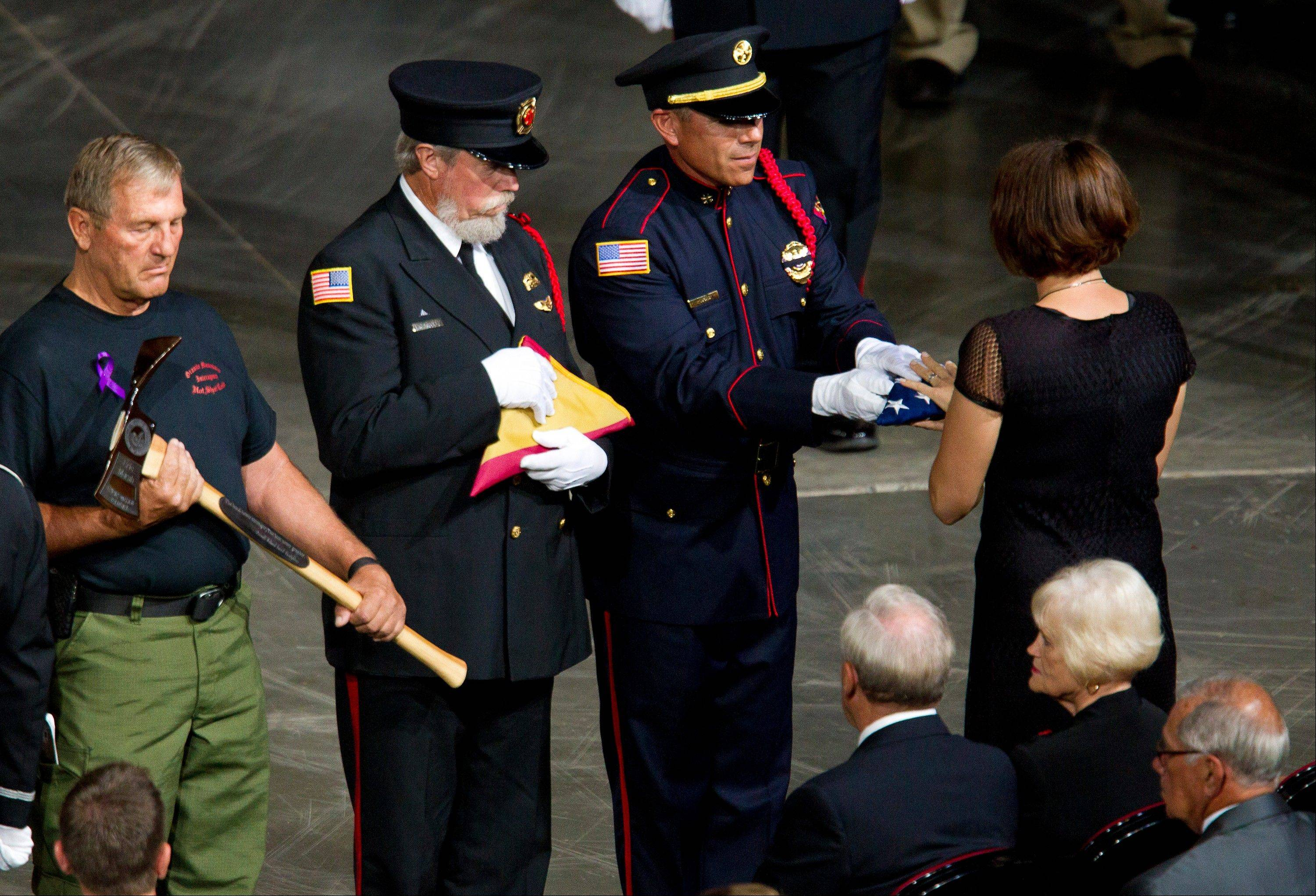A flag is presented to Juliann Ashcraft, widow of fallen firefighter Andrew Ashcraft, during a memorial service for the 19 fallen firefighters at Tim's Toyota Center in Prescott Valley, Ariz. on Tuesday, July 9, 2013.