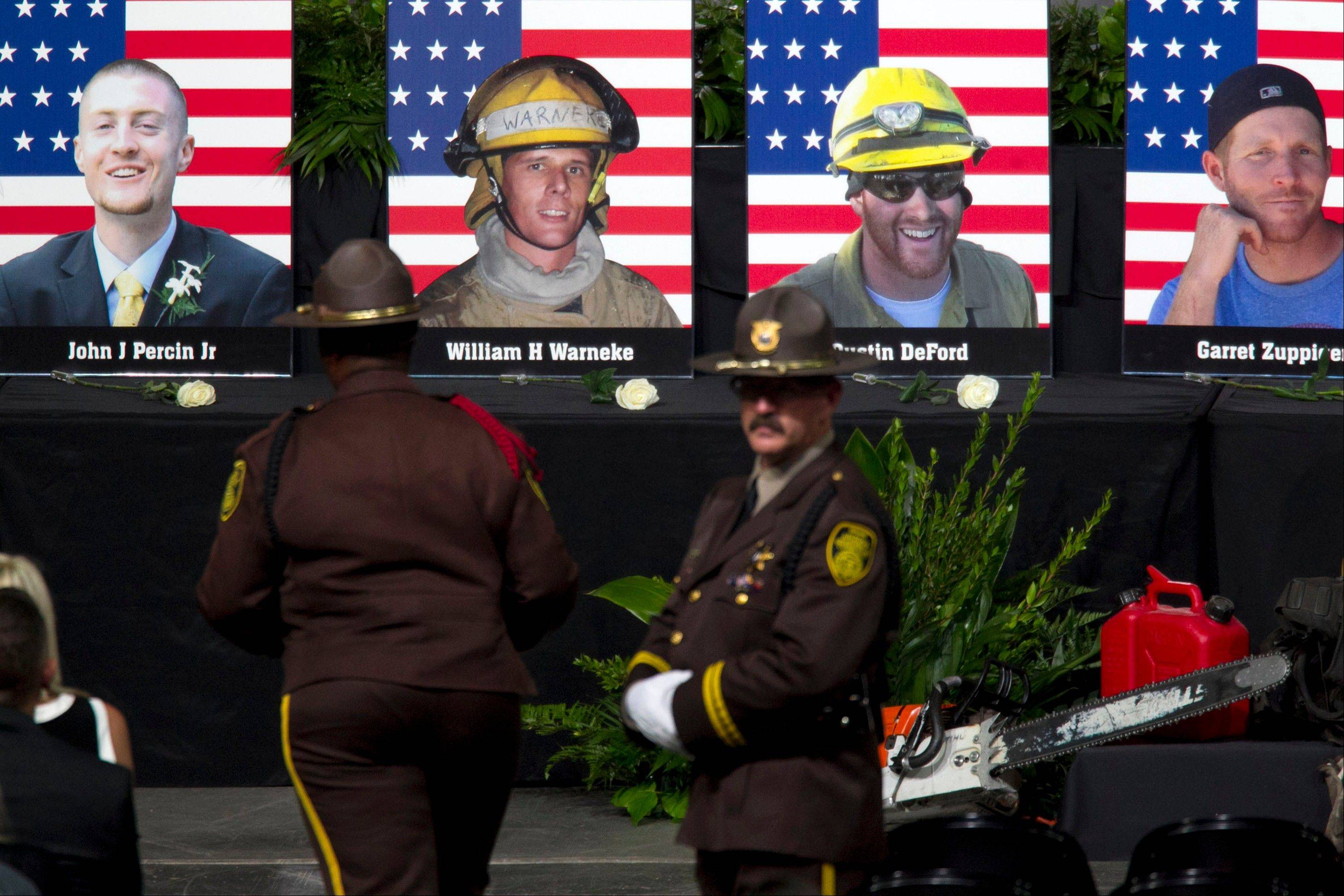 "Photographs of the 19 fallen firefighters are displayed before the ""Our Fallen Brother"" memorial service at Tim's Toyota Center in Prescott Valley, Ariz. on Tuesday, July 9, 2013."