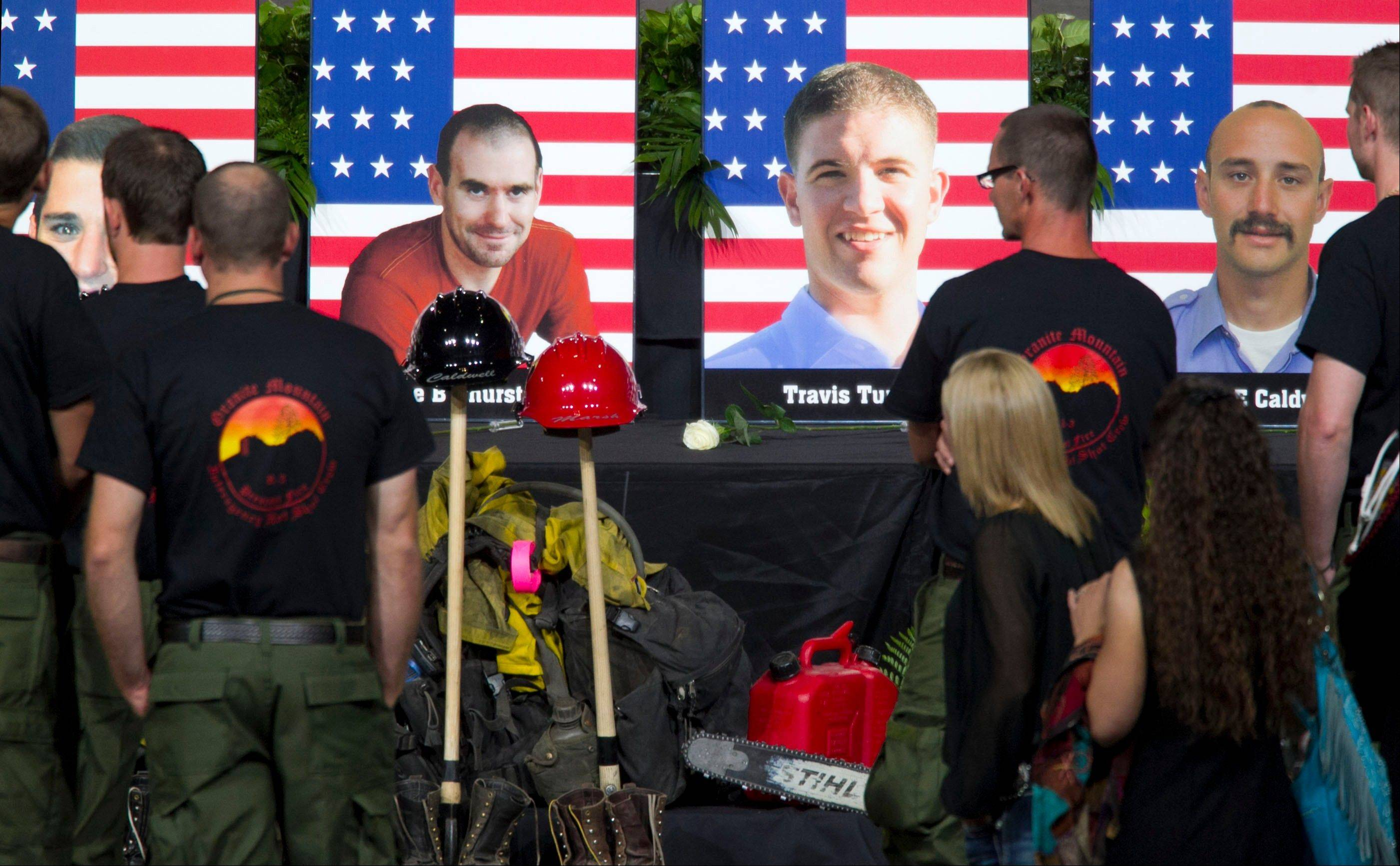 "Alumni of the Granite Mountain Hotshots converse in front of the stage that displays photographs of the 19 fallen firefighters before the ""Our Fallen Brother"" memorial service at Tim's Toyota Center in Prescott Valley, Ariz. on Tuesday, July 9, 2013."