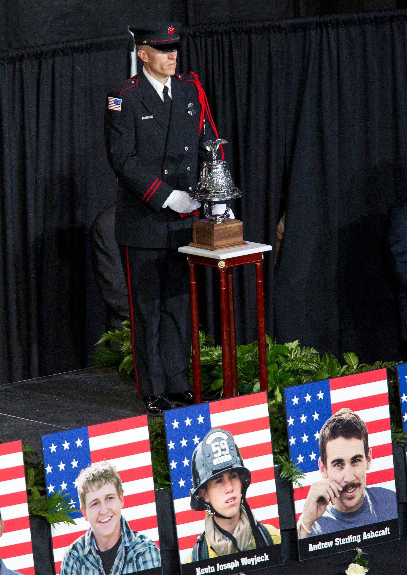 A bell is rung for each fallen firefighter during a memorial service for the 19 fallen firefighters at Tim's Toyota Center in Prescott Valley, Ariz.