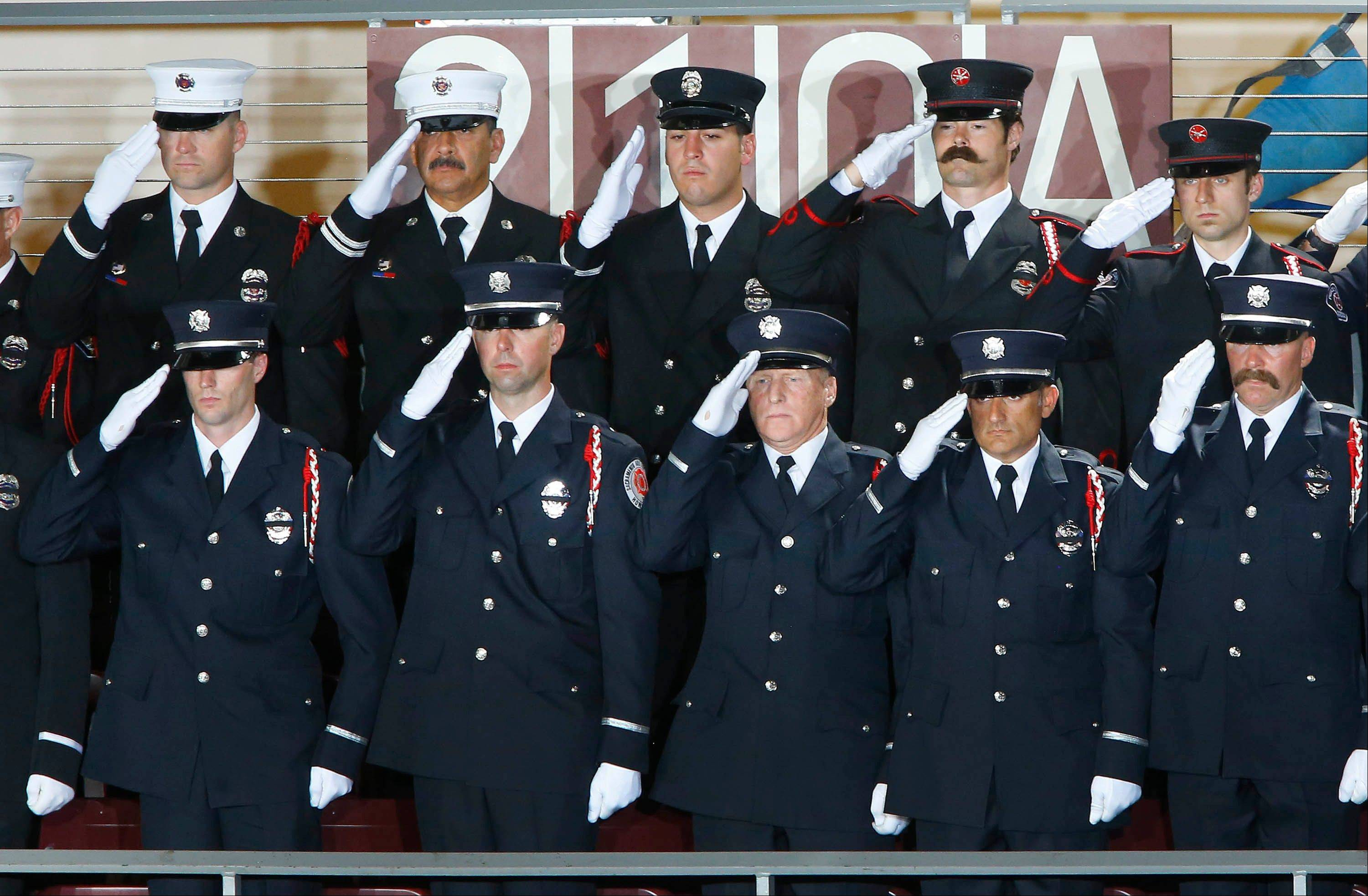 Firefighters from Sacramento, Calif., stand during the National Anthem during a memorial service for the 19 fallen firefighters at Tim's Toyota Center in Prescott Valley, Ariz. on Tuesday, July 9, 2013.
