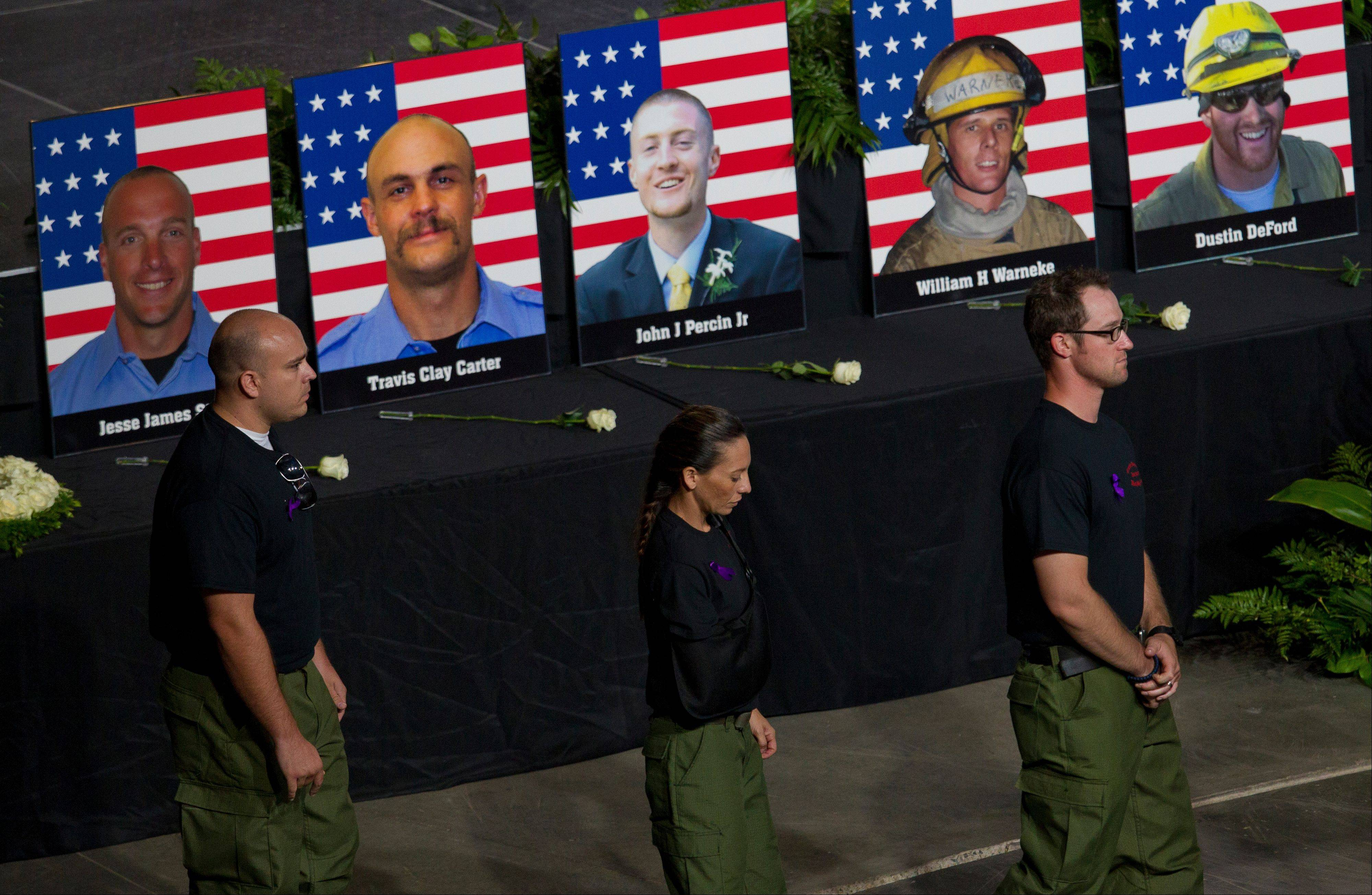 Former Granite Mountain Hotshot firefighters walk past photos of the 19 fallen firefighters during a memorial service at Tim's Toyota Center in Prescott Valley, Ariz. on Tuesday, July 9, 2013.