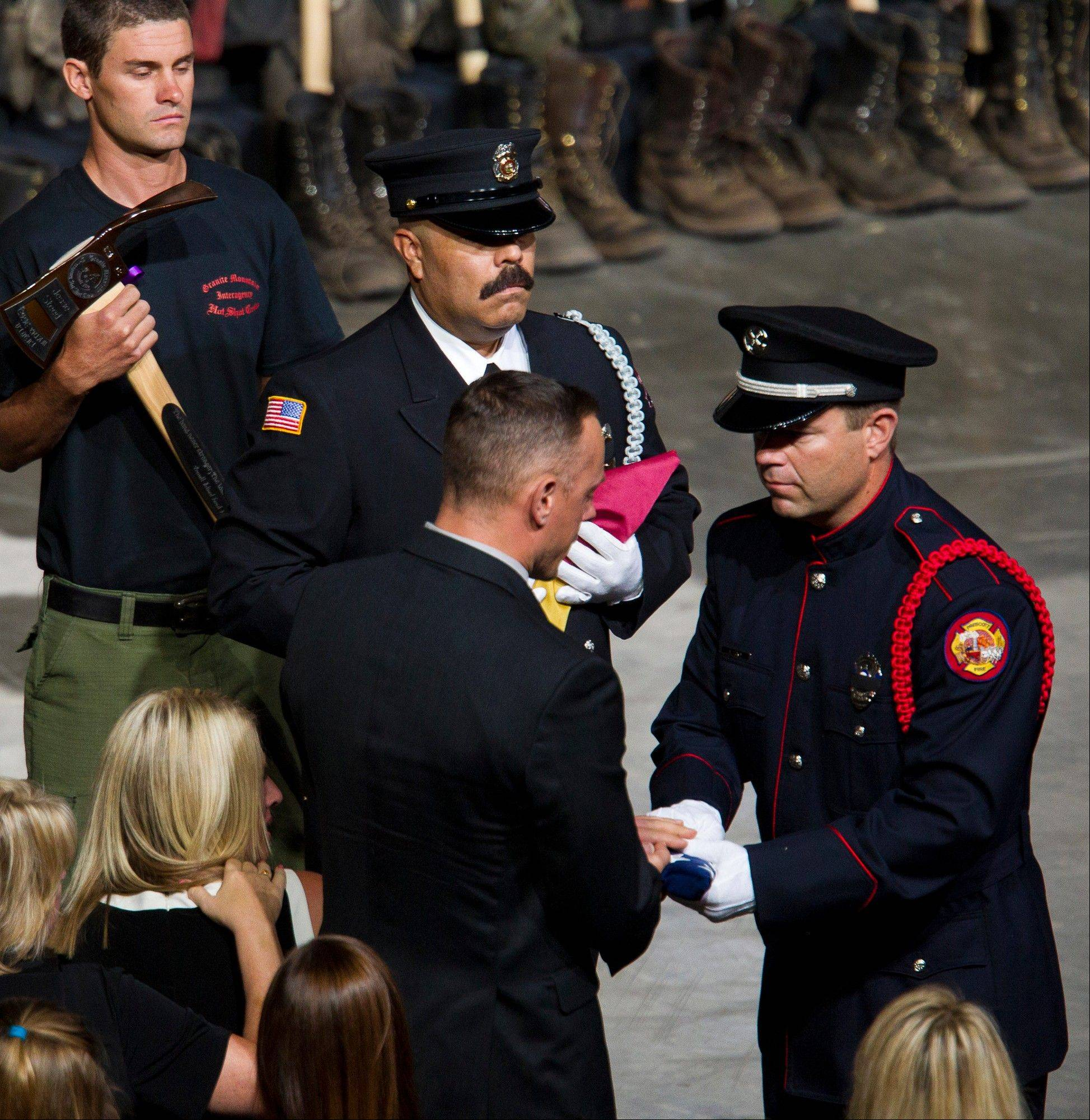 A flag is presented to the family of fallen firefighter Jesse Steed during a memorial service for the 19 fallen firefighters at Tim's Toyota Center in Prescott Valley, Ariz. on Tuesday, July 9, 2013.