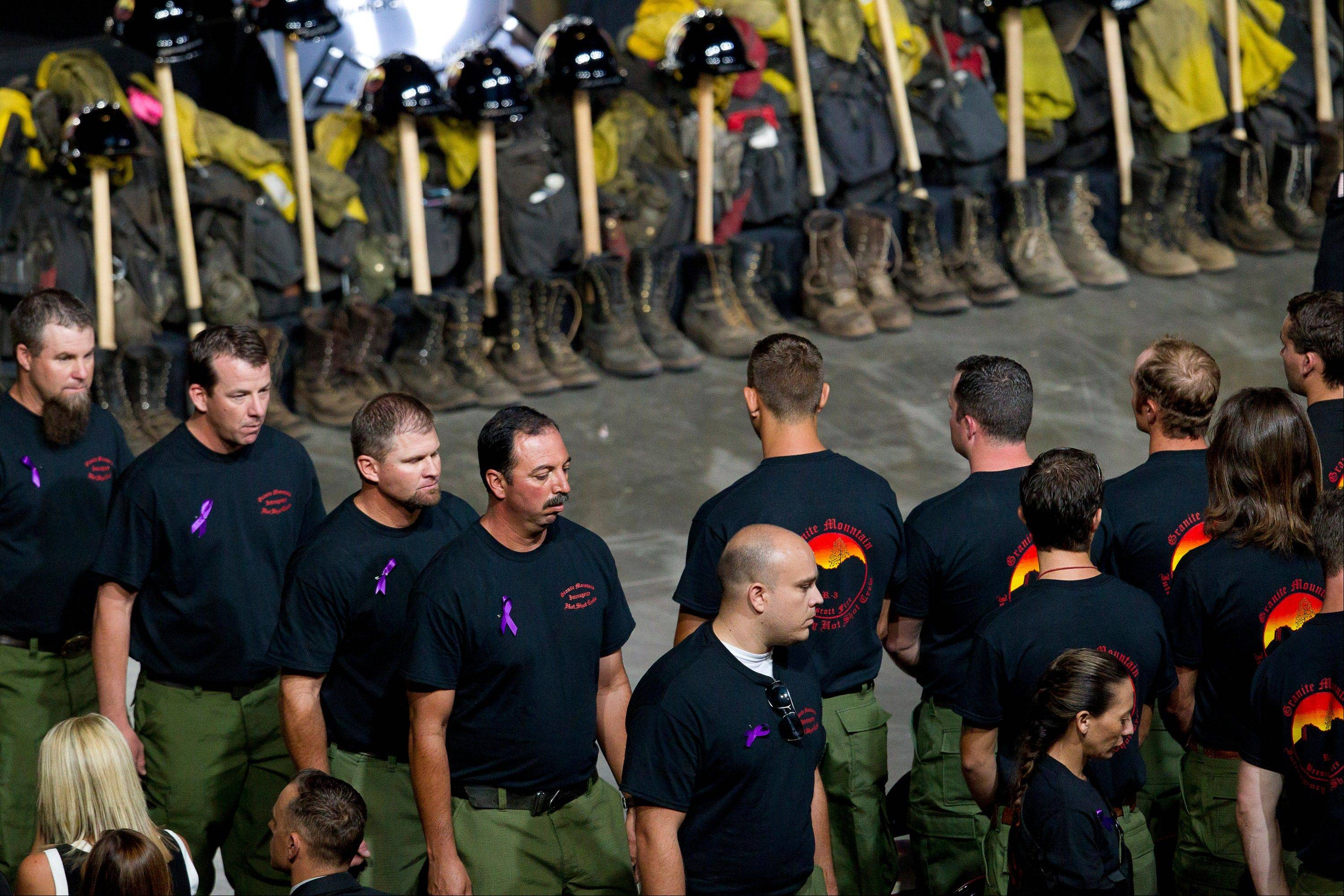 Former Granite Mountain Hotshot firefighters walk past ceremonial firefighter boots and clothing during a memorial service for the 19 fallen firefighters at Tim's Toyota Center in Prescott Valley, Ariz. on Tuesday, July 9, 2013.