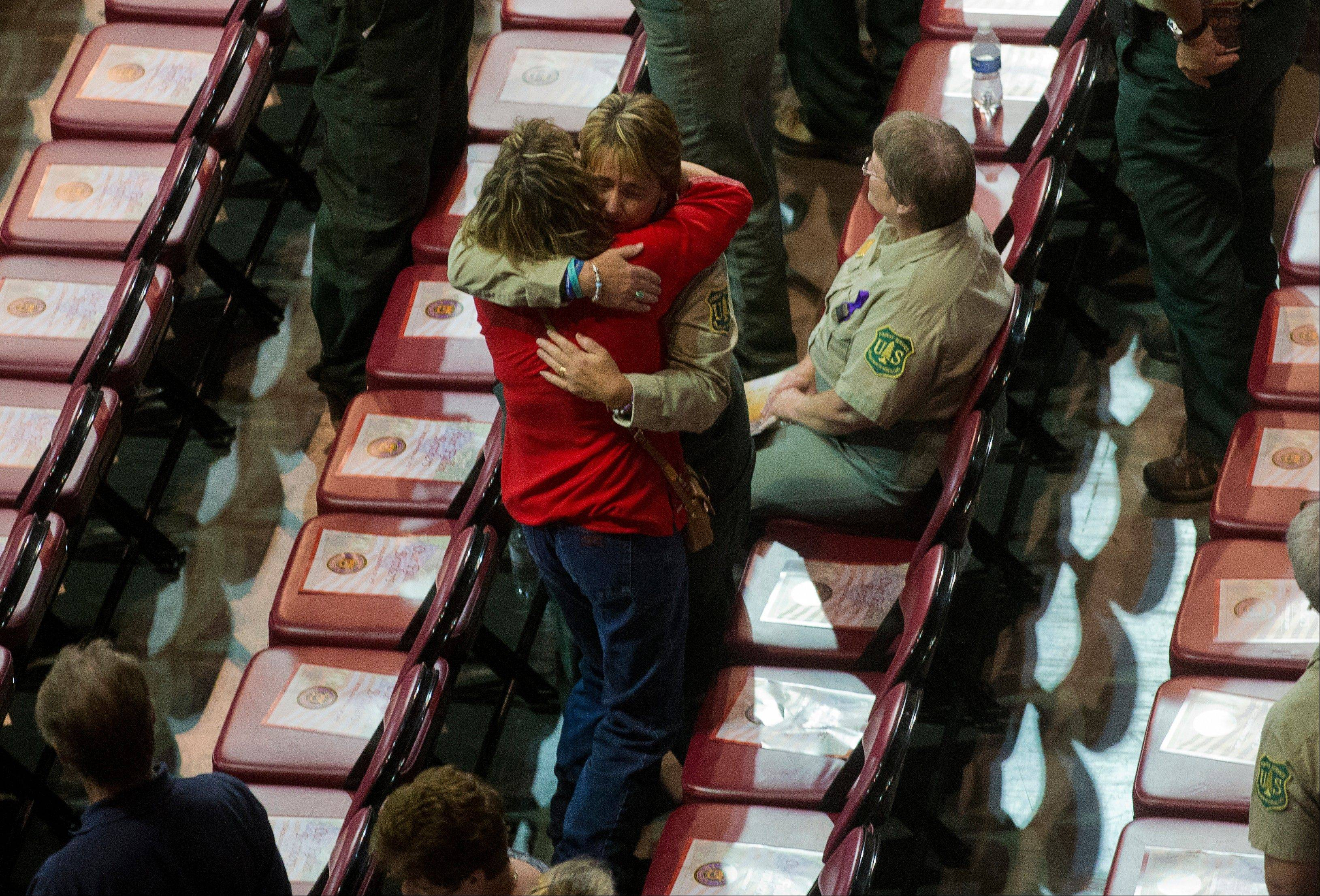 A Prescott National Forrest worker gets a hug from an unidentified woman before a memorial service for the 19 fallen firefighters at Tim's Toyota Center in Prescott Valley, Ariz. on Tuesday, July 9, 2013.