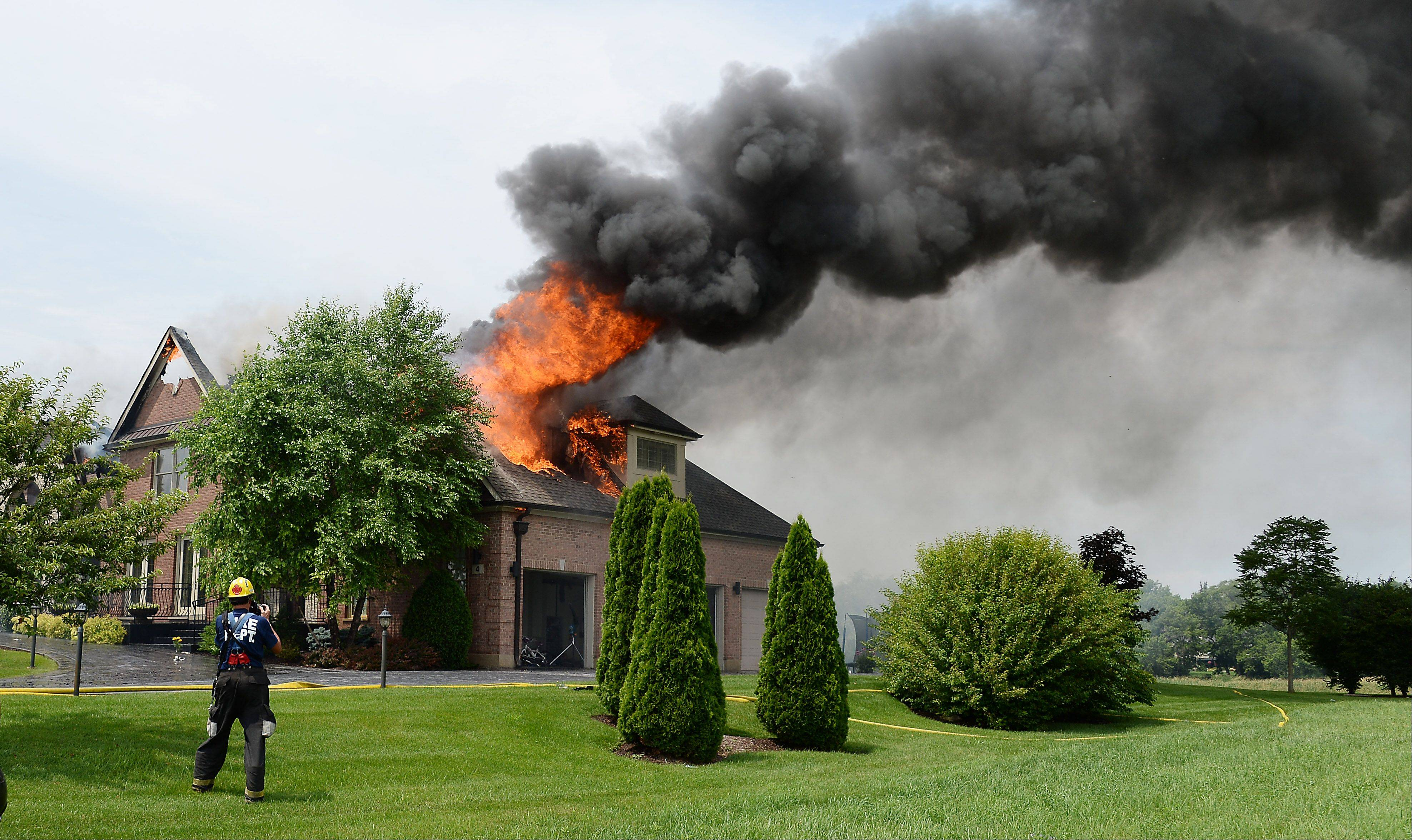 Flames rage on the roof of the house on Terra Vita Drive on Tuesday in South Barrington.