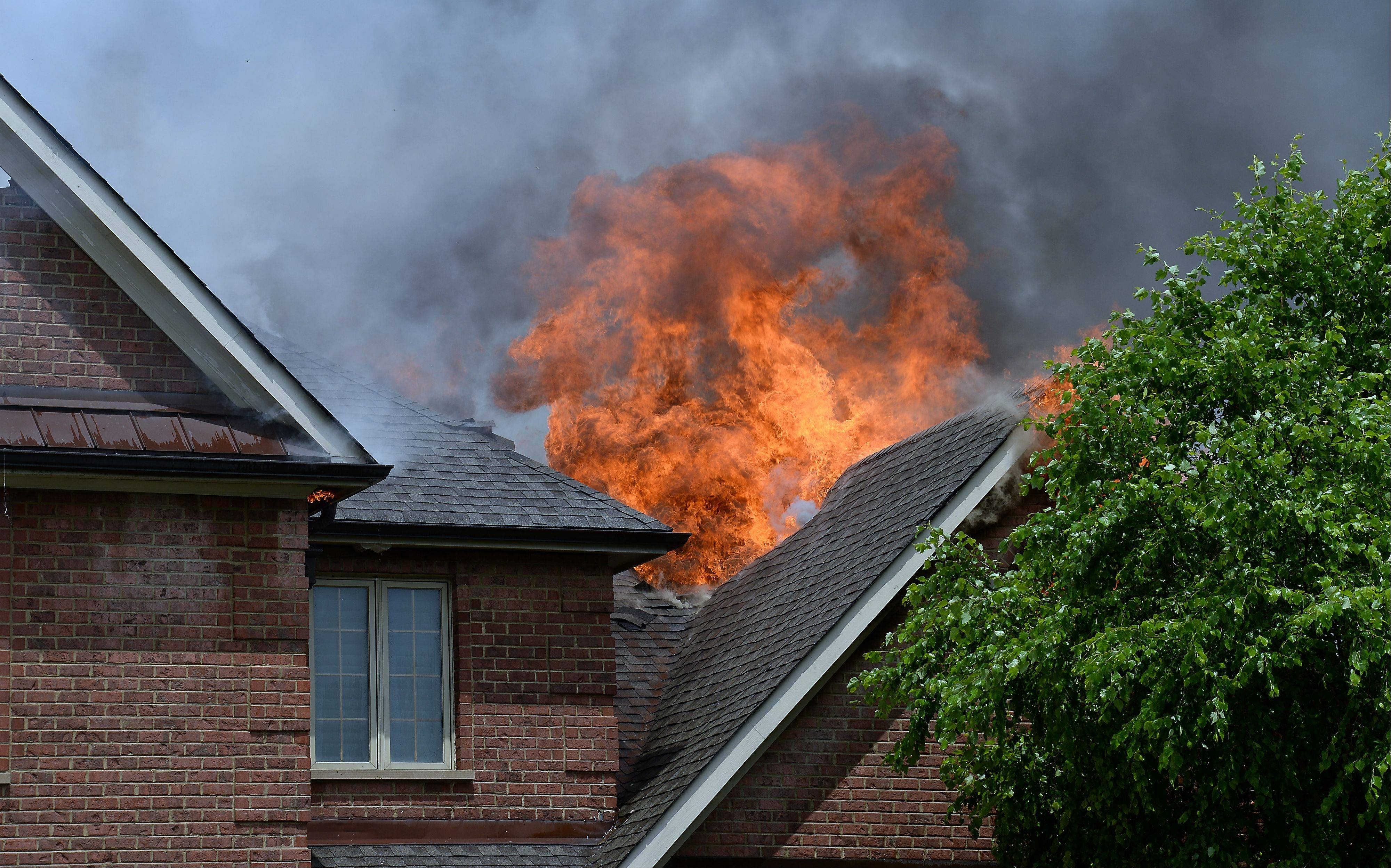 Flames shoot up from behind the home.