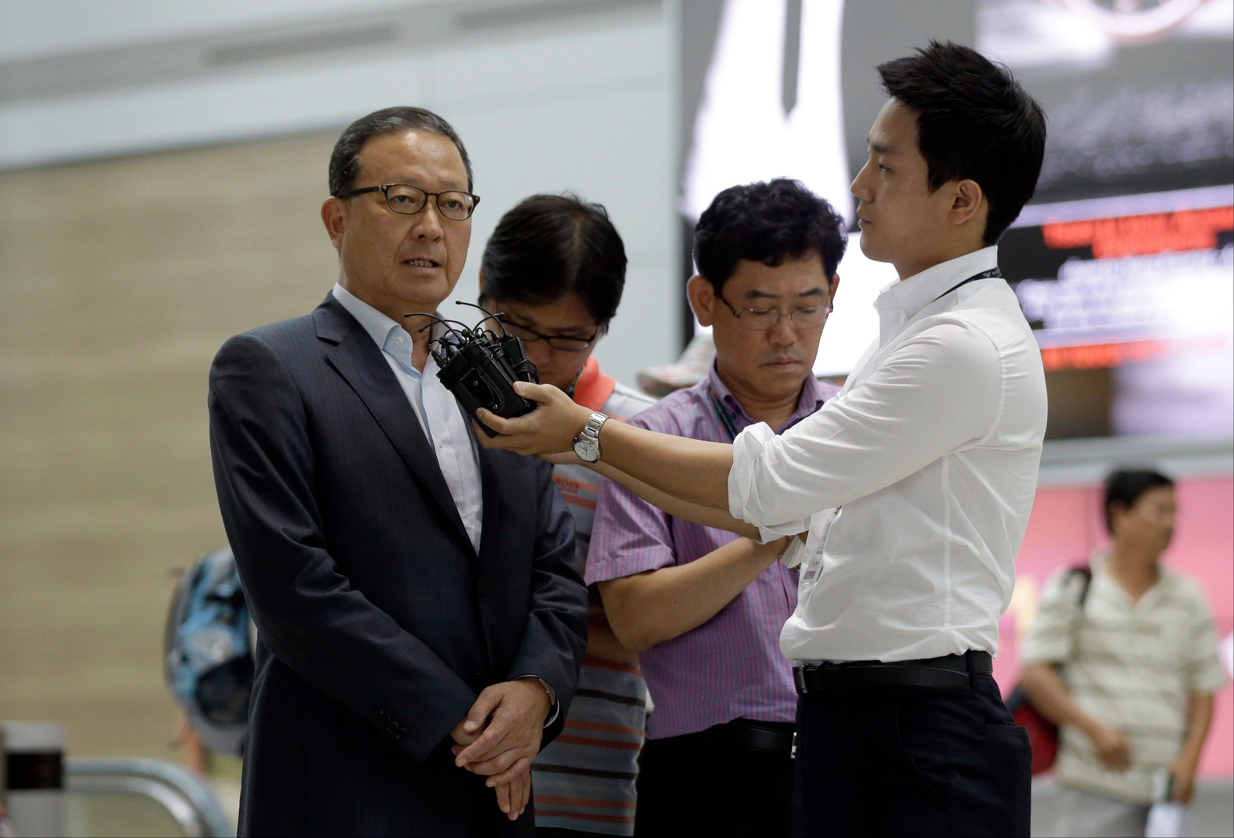 Asiana Airlines President and CEO Yoon Young-doo, left, answers reporters' questions before heading to San Francisco at the flight gate of the Incheon International Airport in Incheon, west of Seoul, South Korea, Tuesday, July 9, 2013. A South Korean official says both U.S. and Korean investigators have been interviewing the pilots who were in the cockpit when an Asiana Airlines plane clipped a sea wall before crash landing at San Francisco International Airport Saturday.