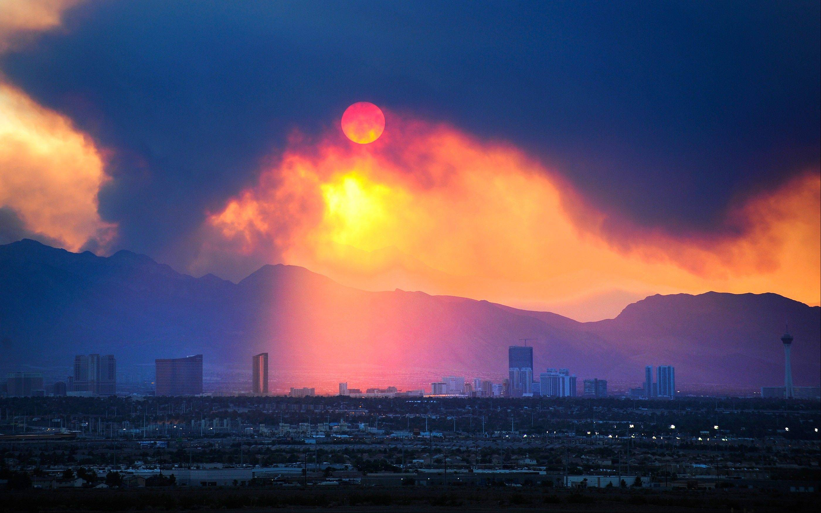The Las Vegas Strip skyline is seen as smoke continues to billow from the Carpenter 1 fire on Mount Charleston on Monday, July 8, 2013 in Las Vegas. Homes were threatened, but more than 750 firefighters, including 18 elite Hotshot crews, were battling the Carpenter 1 Fire some 25 miles northwest of Las Vegas, said Jay Nichols, a U.S. Forest Service spokesman in the Spring Mountains National Recreation Area.