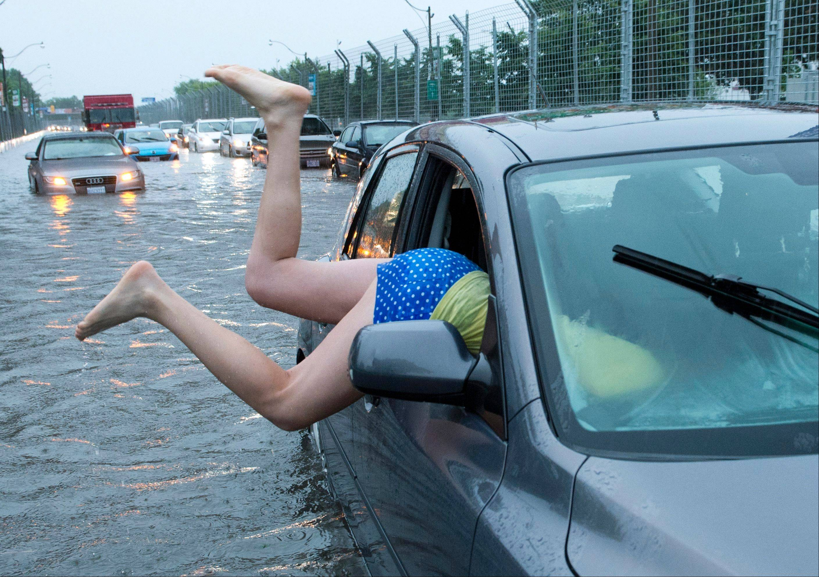 A woman gets back into her flooded car on the Toronto Indy course on Lakeshore Boulevard in Toronto on Monday, July 8 2013.