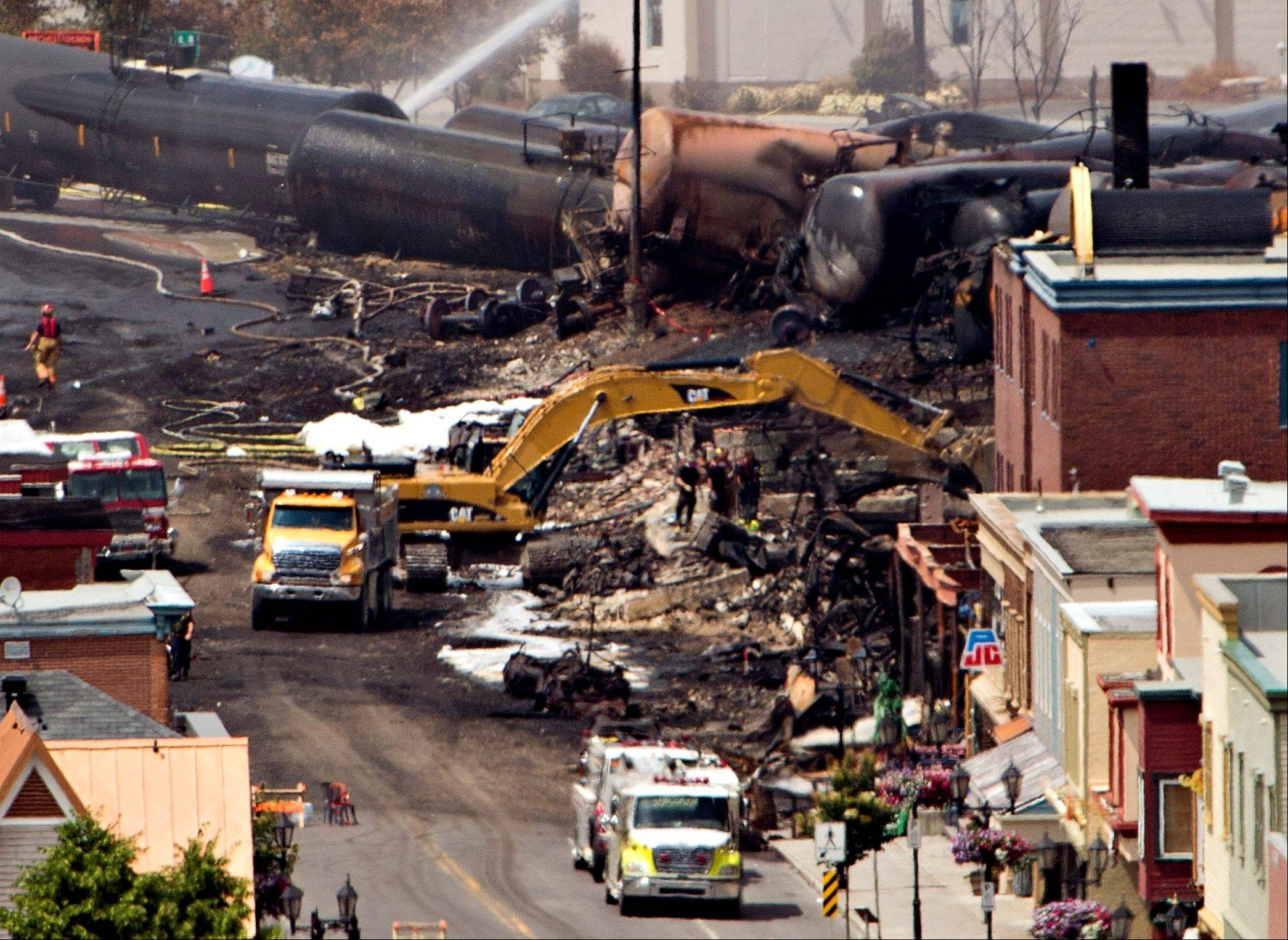Searchers dig through the rubble for victims in Lac-Megantic, Quebec, Monday, after a runaway train derailed early Saturday igniting tanker cars carrying crude oil. The train is owned by Montreal, Maine & Atlantic Railway, whose parent company Rail World, Inc., is based in Rosemont.