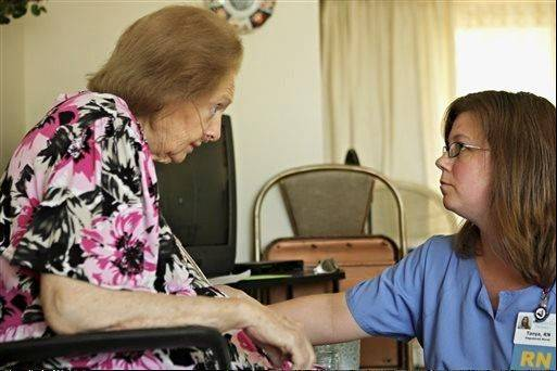 Hospice patient Jocelyn Green, left, discusses medications with registered nurse Tanya Diedrich, of DeKalb County Hospice, at Green's home in DeKalb.