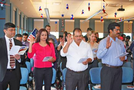 U.S. citizens-to-be take the Naturalization Oath during a Citizenship Ceremony at the Schaumburg Township District Library.