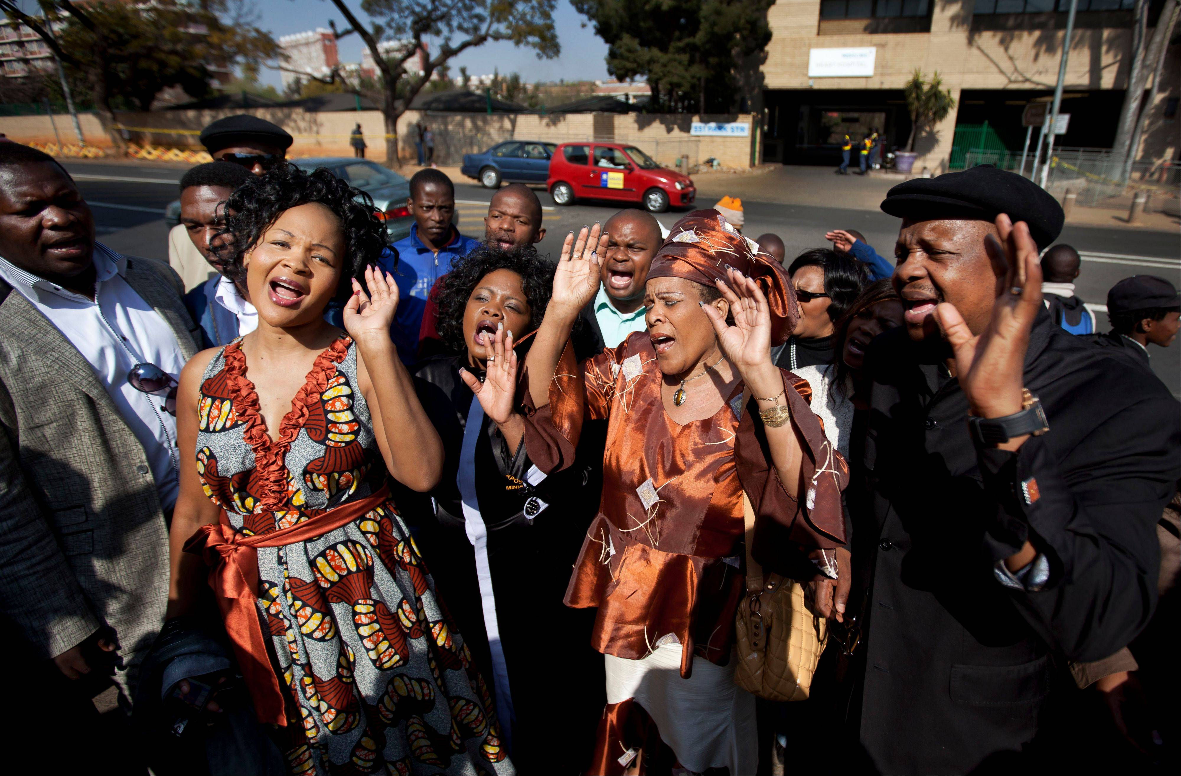 A group of gospel singers pay tribute outside the entrance to the Mediclinic Heart Hospital where former South African President Nelson Mandela is being treated in Pretoria, South Africa. The Nelson Mandela Foundation is hoping that volunteers around the world will donate 67 minutes of their time when South Africa�s former president turns 95 next week.