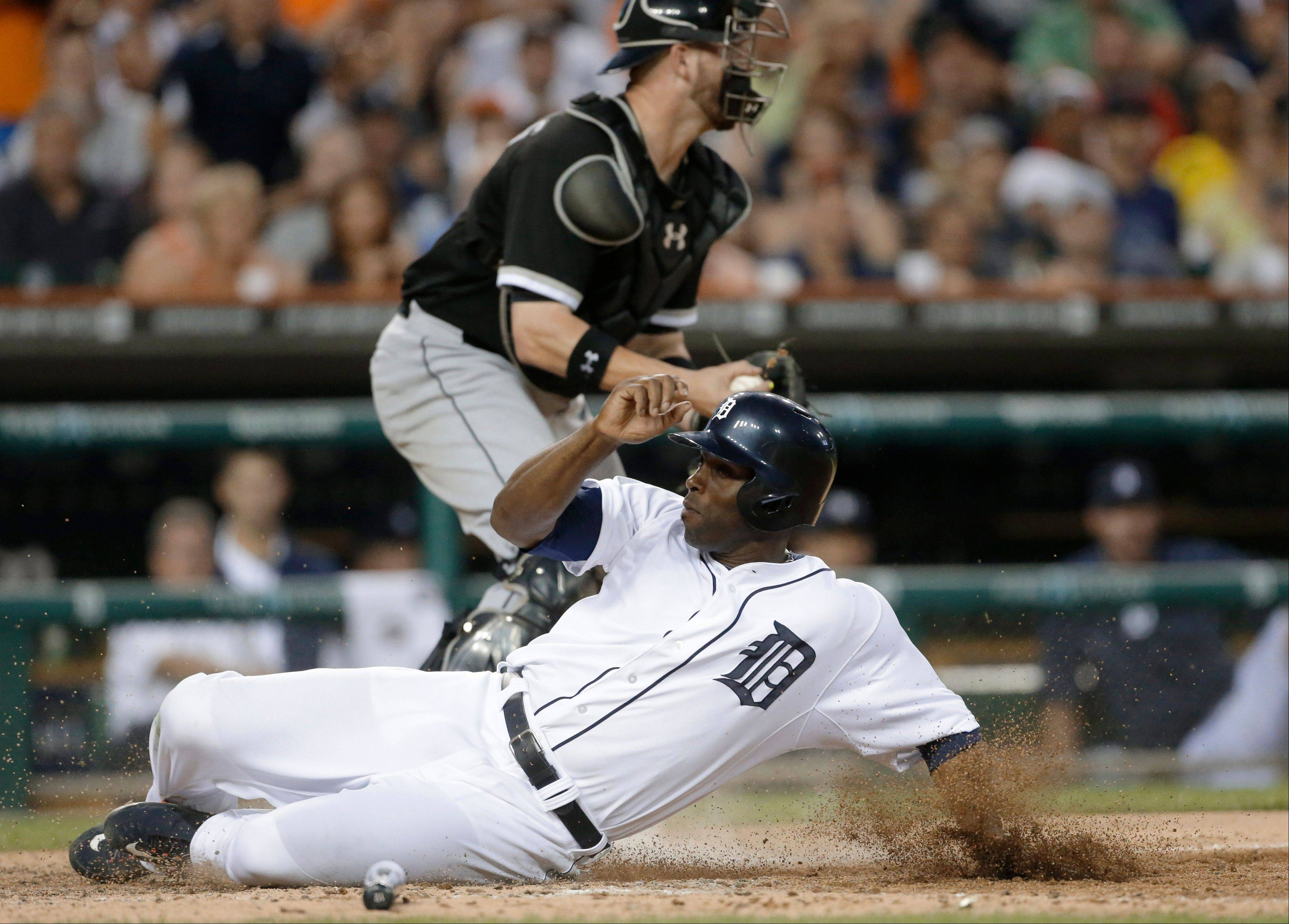 Detroit Tigers' Torii Hunter beats the throw to Chicago White Sox catcher Tyler Flowers from left fielder Dayan Viciedo and scores from second on a single by Prince Fielder during the sixth inning of a baseball game in Detroit, Wednesday, July 10, 2013. (AP Photo/Carlos Osorio)