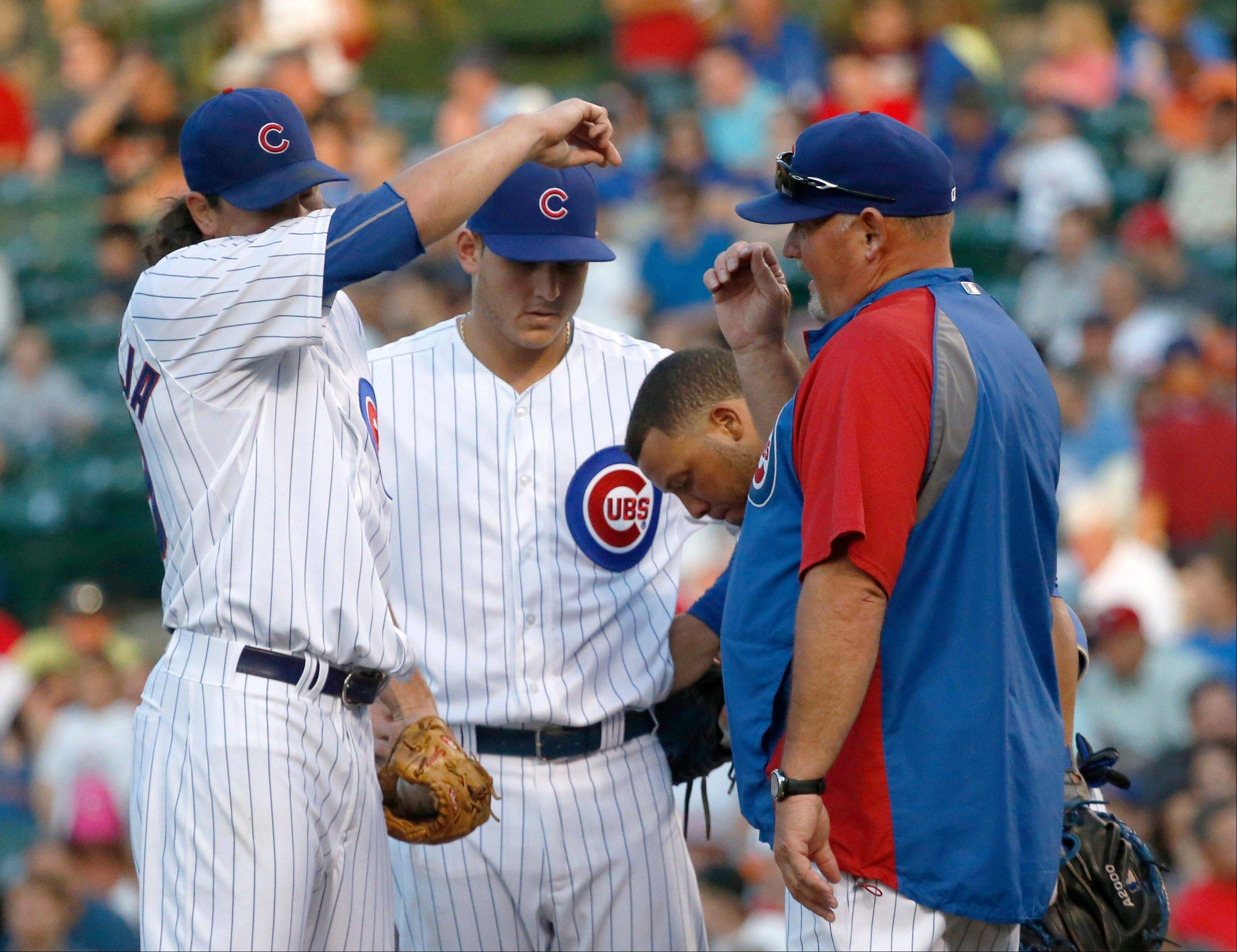 Cubs starting pitcher Jeff Samardzija, left, wipes the sweat from his face as he listens to pitching coach Chris Bosio, right, with first baseman Anthony Rizzo and catcher Welington Castillo joining them at the mound during Wednesday's first inning at Wrigley Field.
